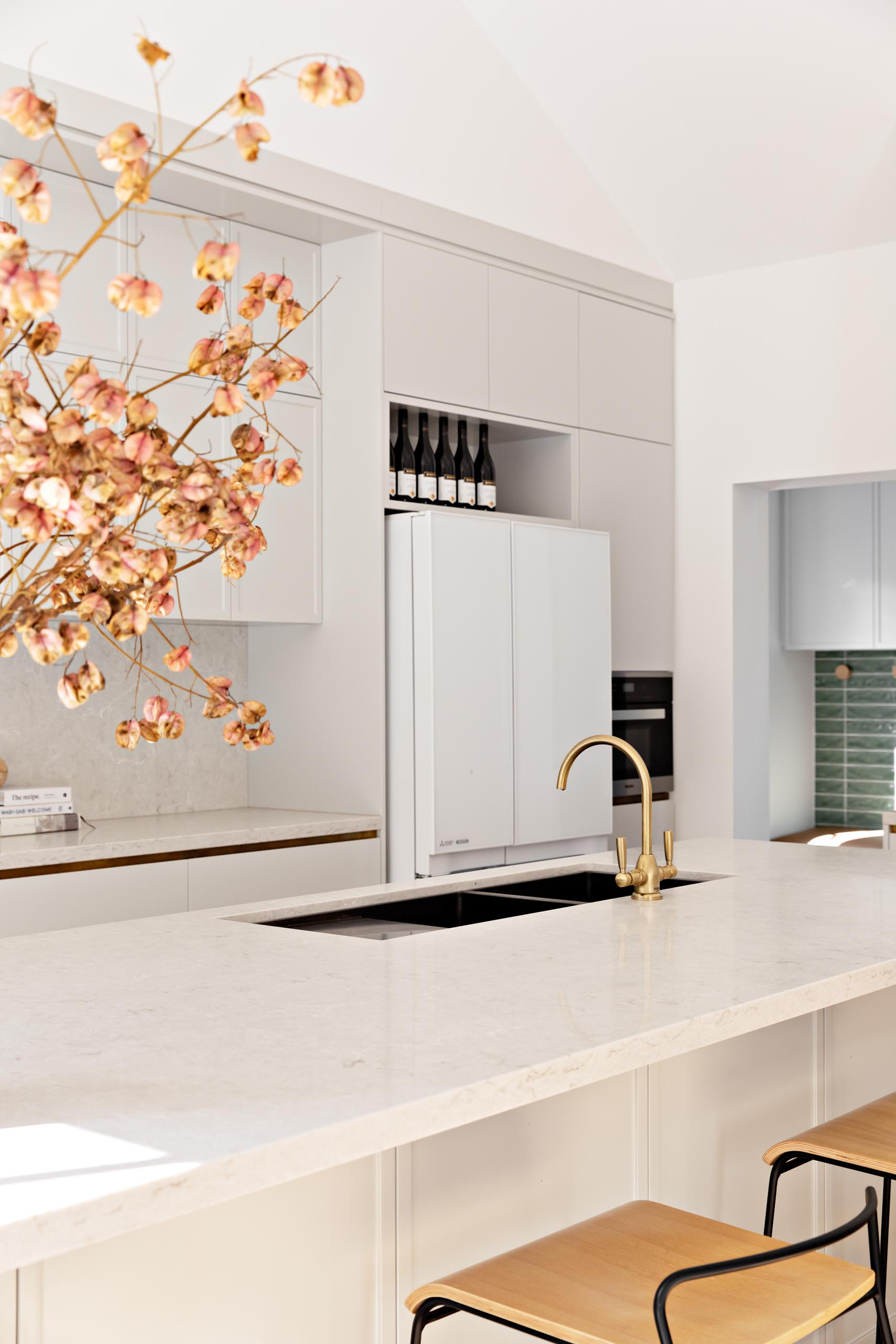 A modern kitchen with light grey cabinets, a long island, and light stone countertops.