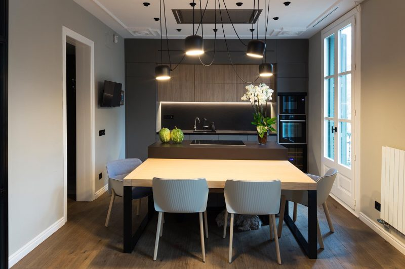 This modern flexible kitchen and dining room has dark cabinetry and island, which is contrasted by the light wood dining table, which can be moved.
