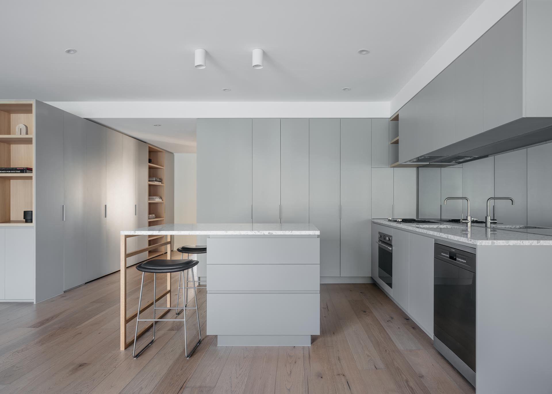 A modern kitchen with minimalist light gray cabinets and an island.