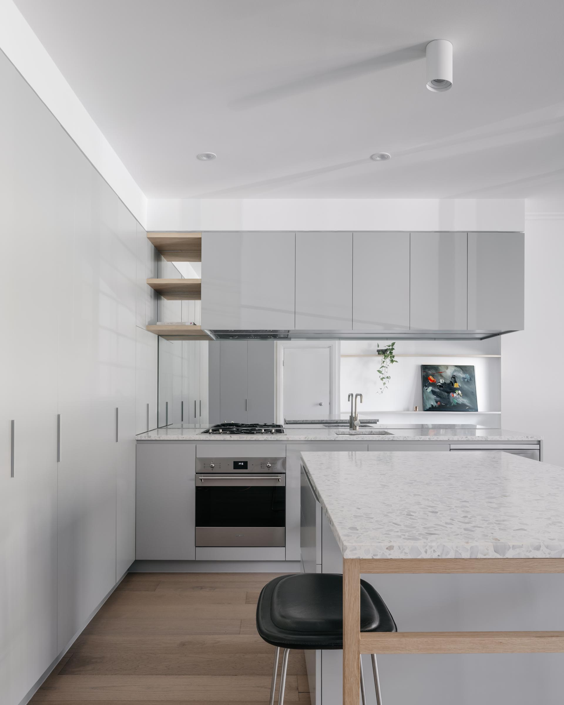 A modern kitchen with minimalist gray cabinets, white stone countertops, and oak flooring.