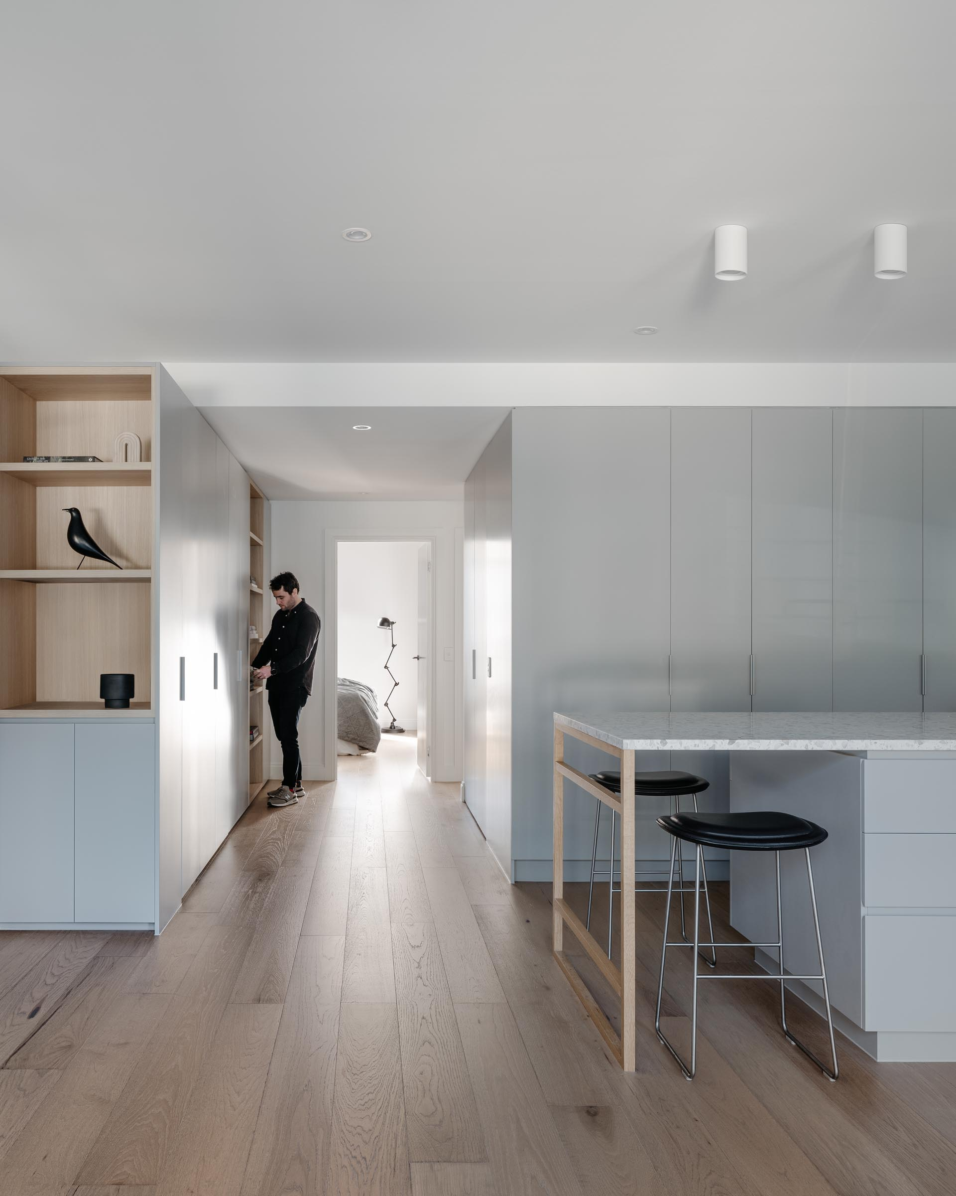 A modern apartment with minimalist light gray cabinets and oak flooring.