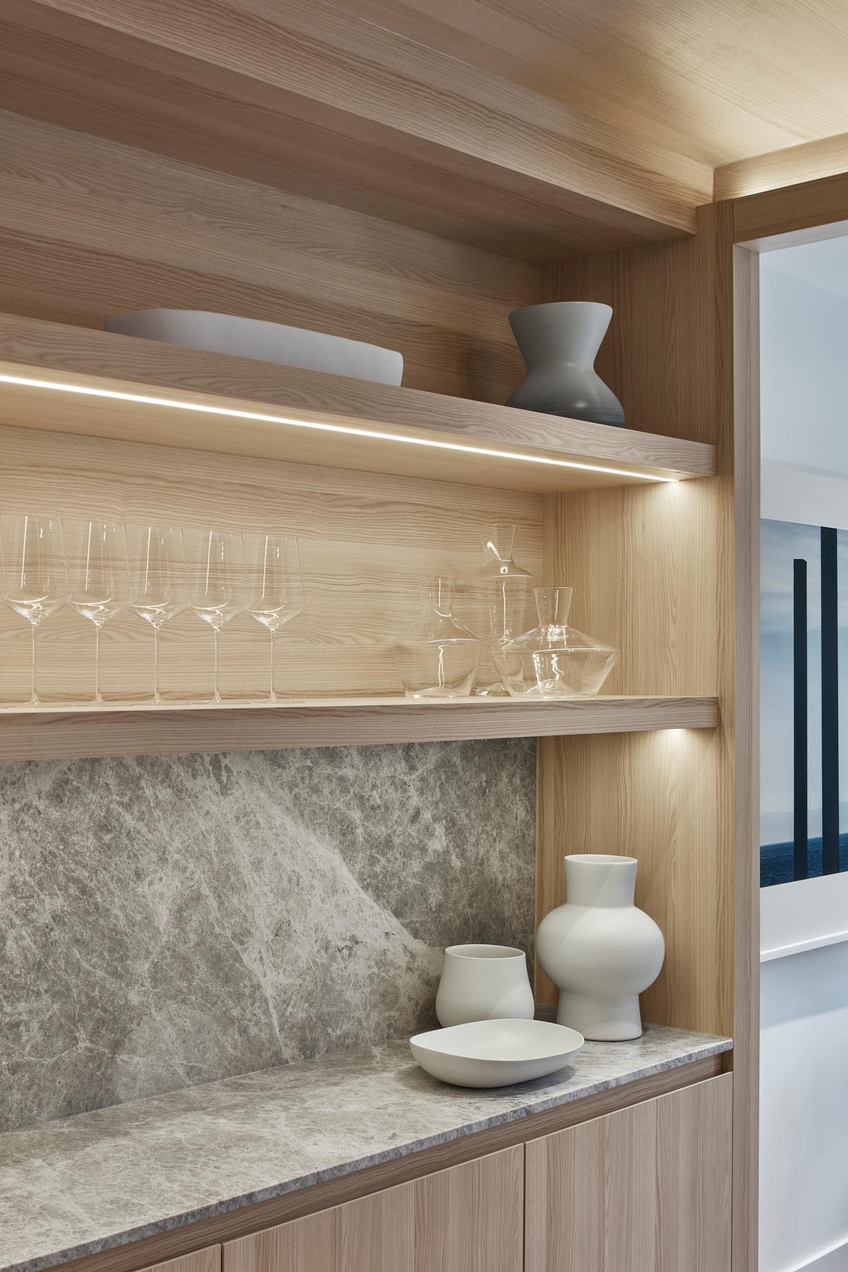 A modern wood kitchen with hidden lighting to show off the items on the shelf below.