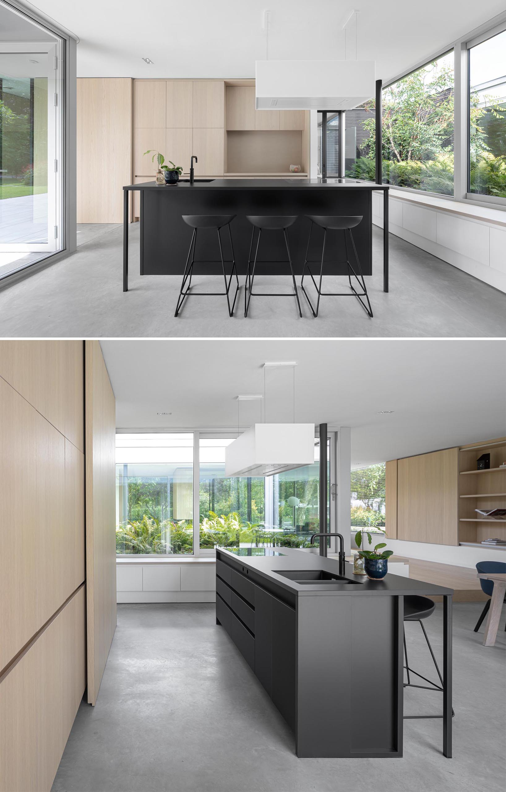 A modern kitchen with minimalist wood cabinets, a matte black island with matching stools, and concrete floors.