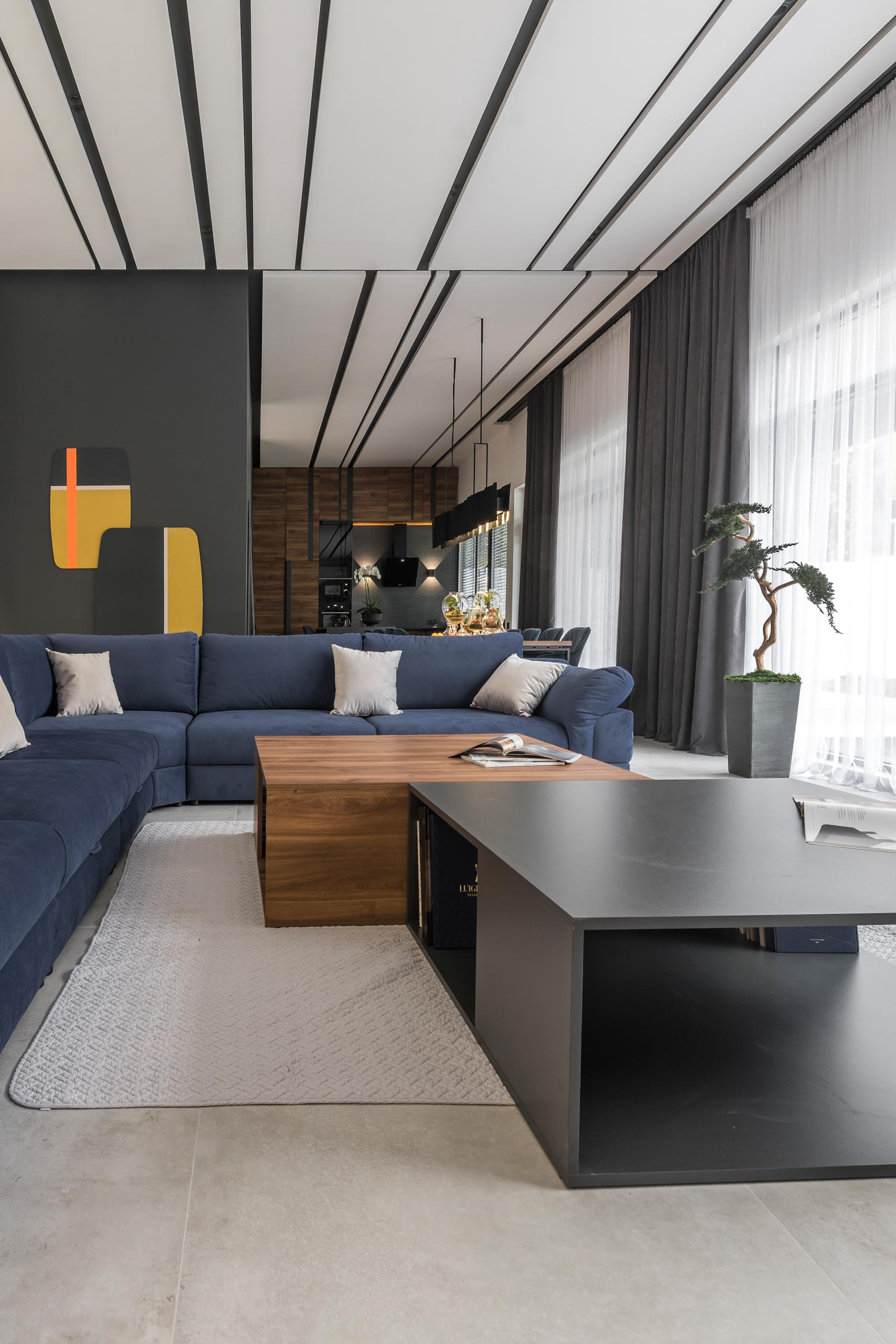 A modern living room with a large blue sofa, and a wood and gray coffee table.