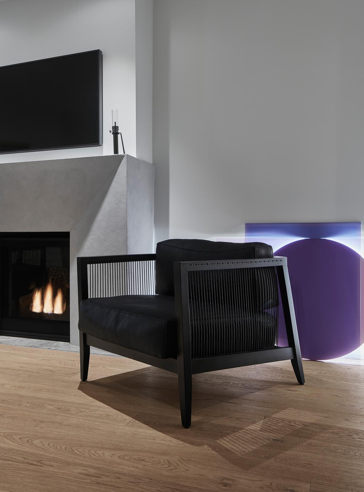 A modern living room with a black armchair, a grey fireplace surround, and wood floors.