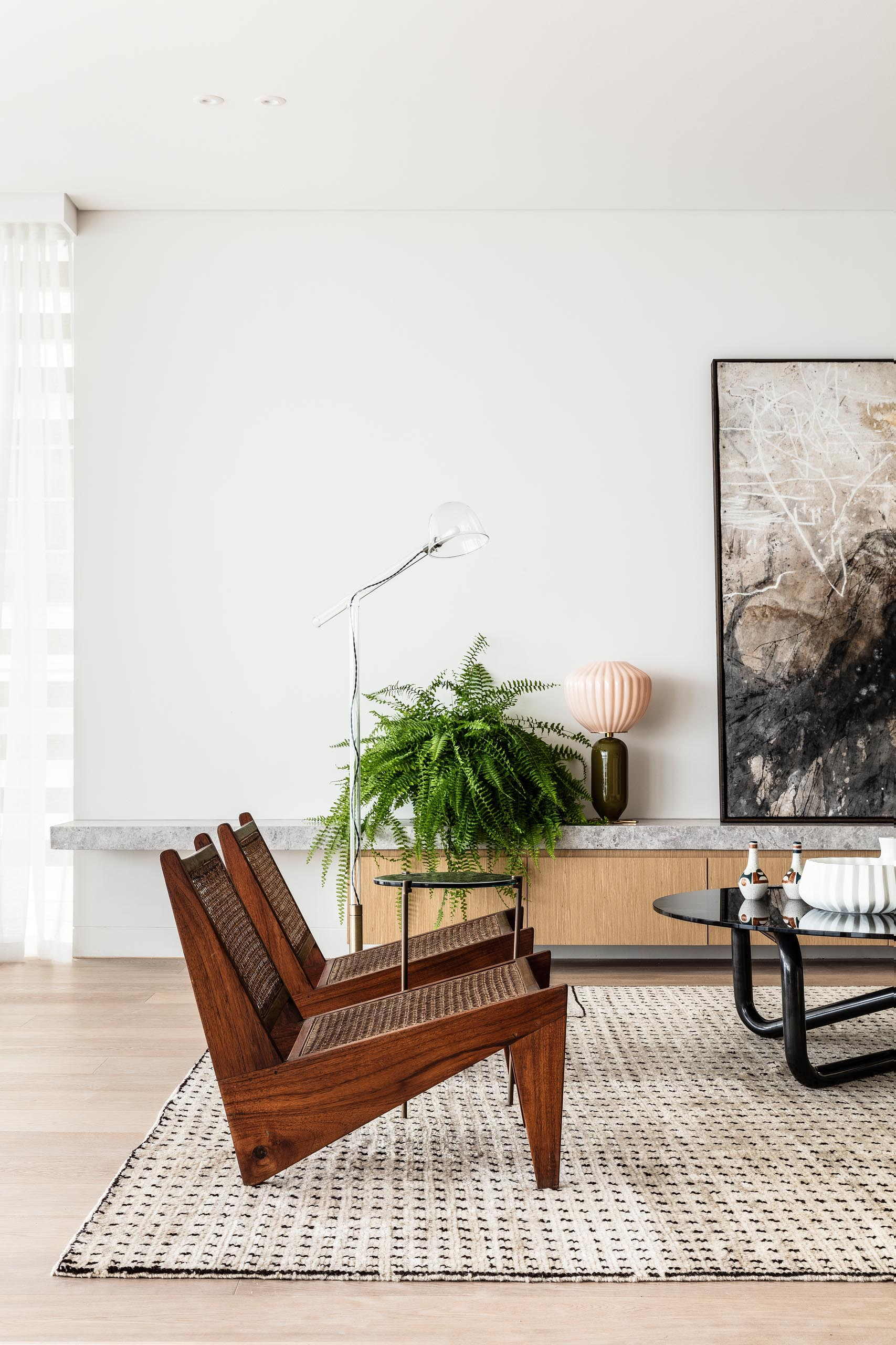 A large rug anchors this living room, while a low cabinet provides a place to display artwork, plants, and decor.