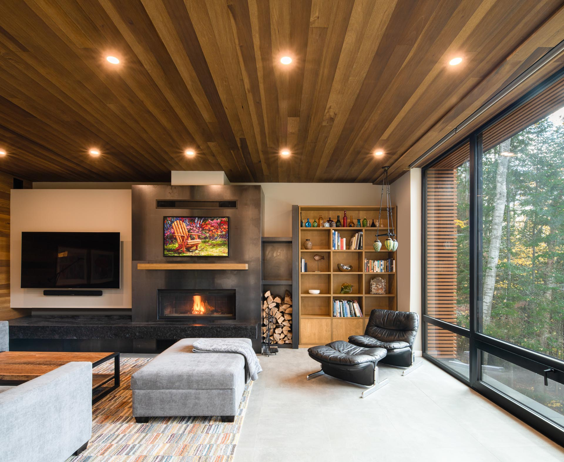 Inside his prefab home, wood has been used to create a space that's warm and welcoming. In the living room, there's a fireplace, a dedicated area for the television, and a bookcase.