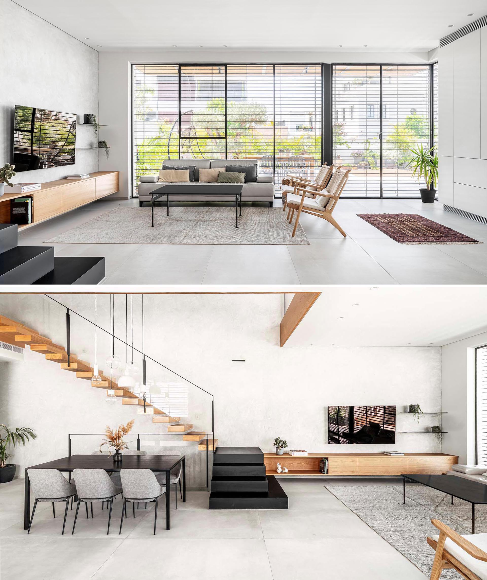 Tall windows line the walls of this modern interior and let in copious amounts of natural light into the open living room, dining area, and kitchen.