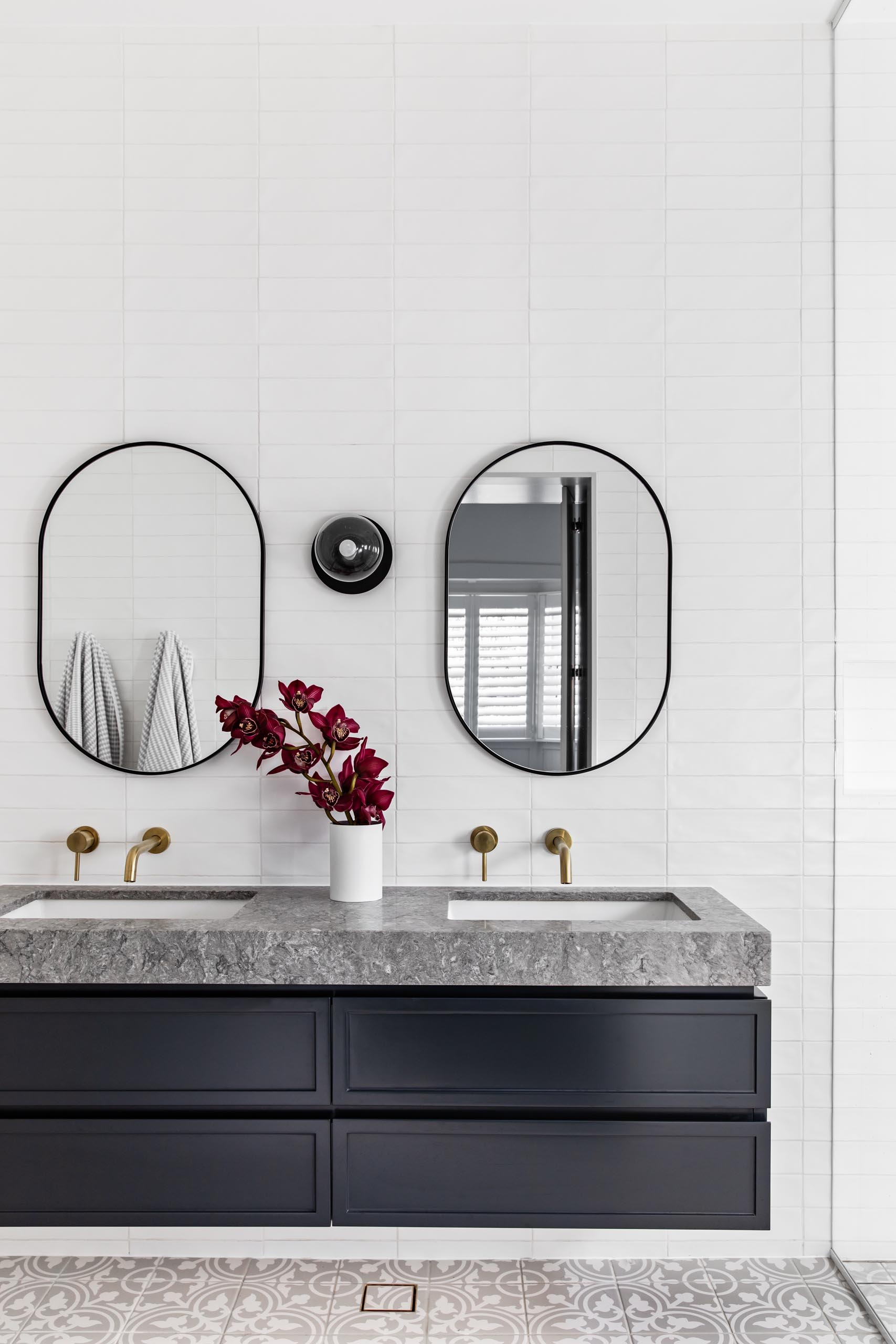A modern bathroom with patterned floor tiles, a floating black vanity topped with grey stone, white subway tiles that cover the walls, oval black-framed mirrors, and brass hardware