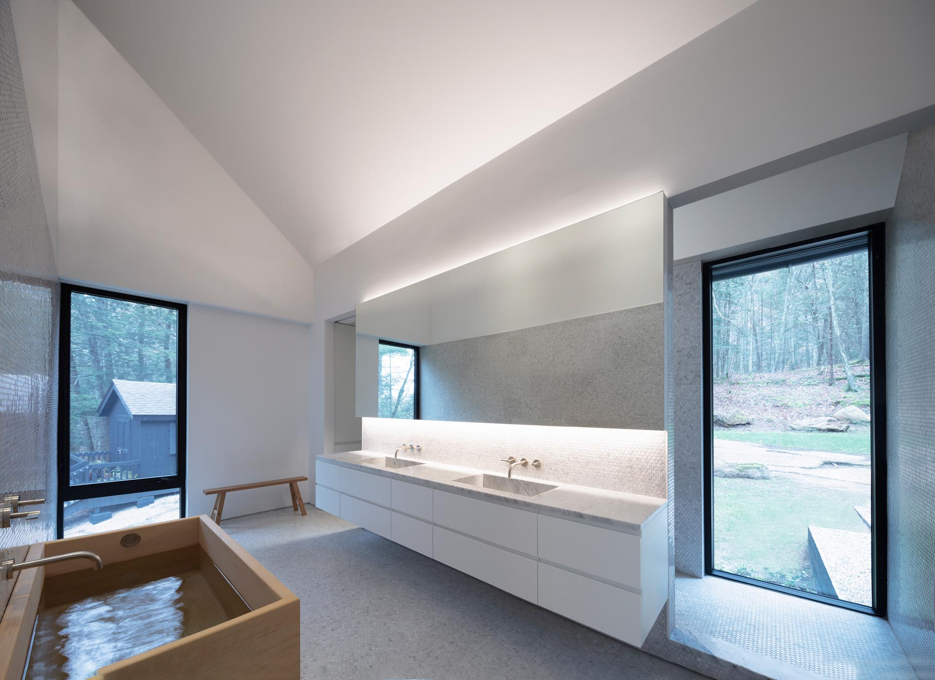 A modern master bathroom with a wood soaking tub, a backlit mirror, a double-sink floating vanity, and a sloped ceiling.