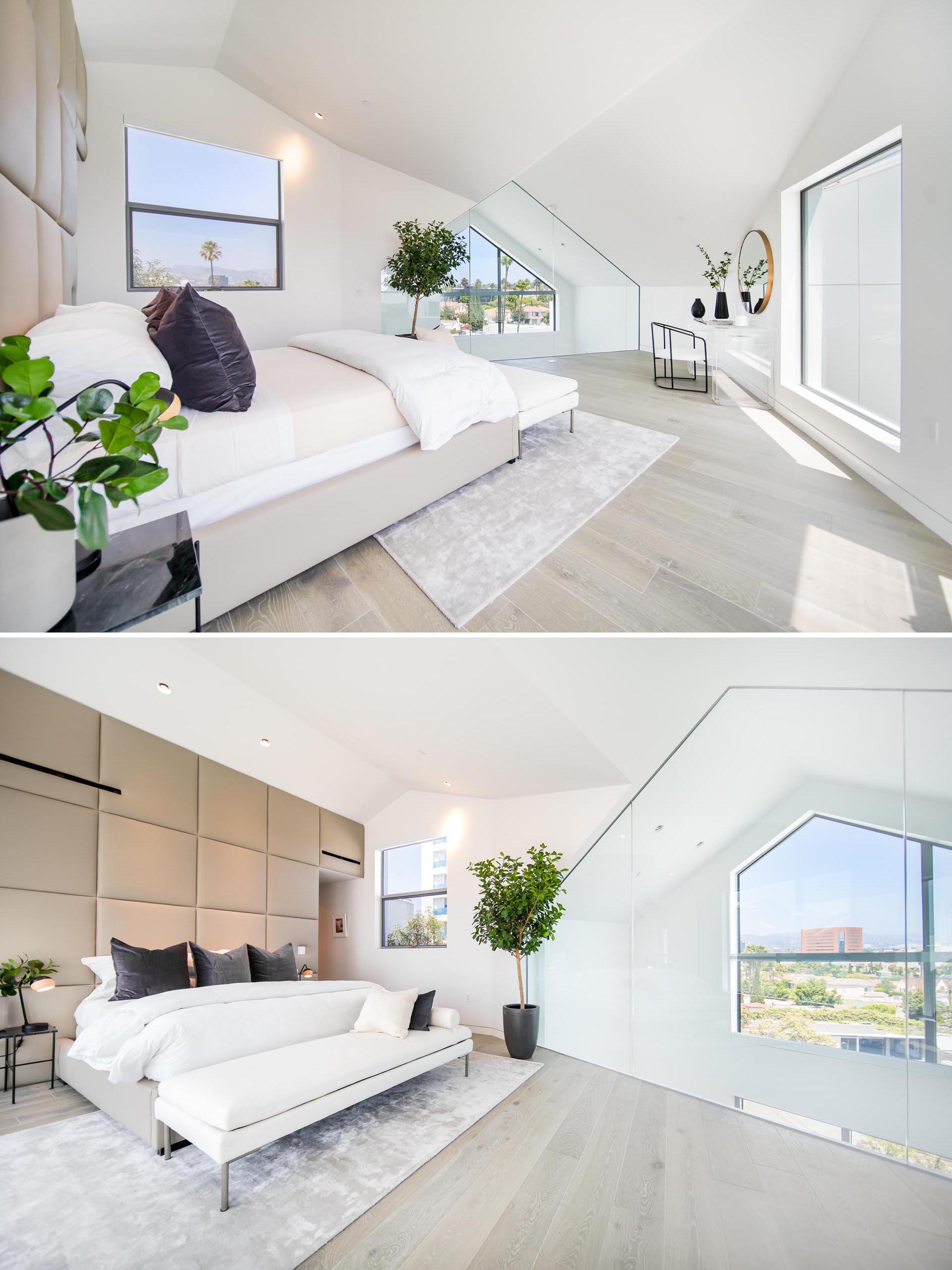 A modern bedroom with upholstered accent wall, and a glass wall that overlooks the living room.