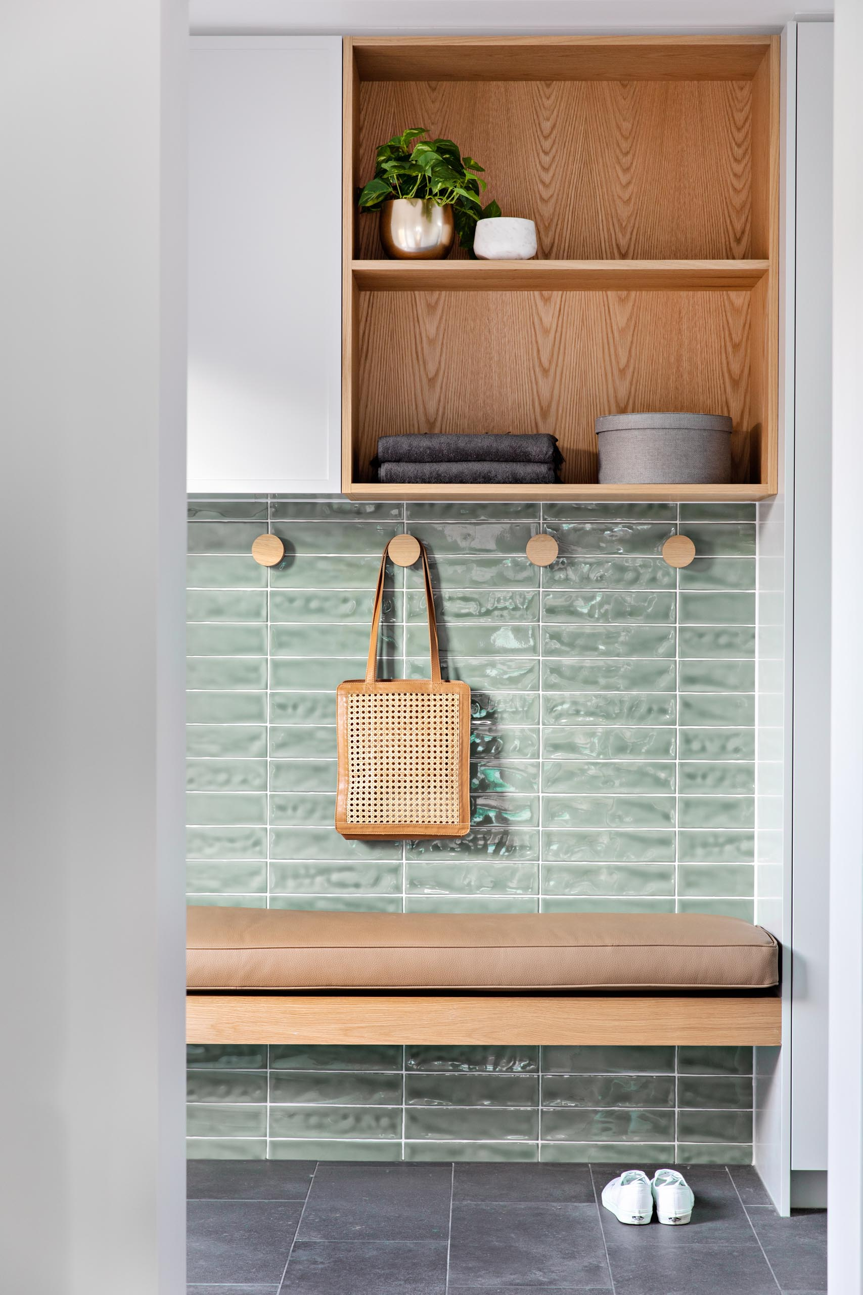 A small mud room with soft green tiles, a wood bench with brown leather cushion, round wood hooks, and a cabinet with open wood shelving.