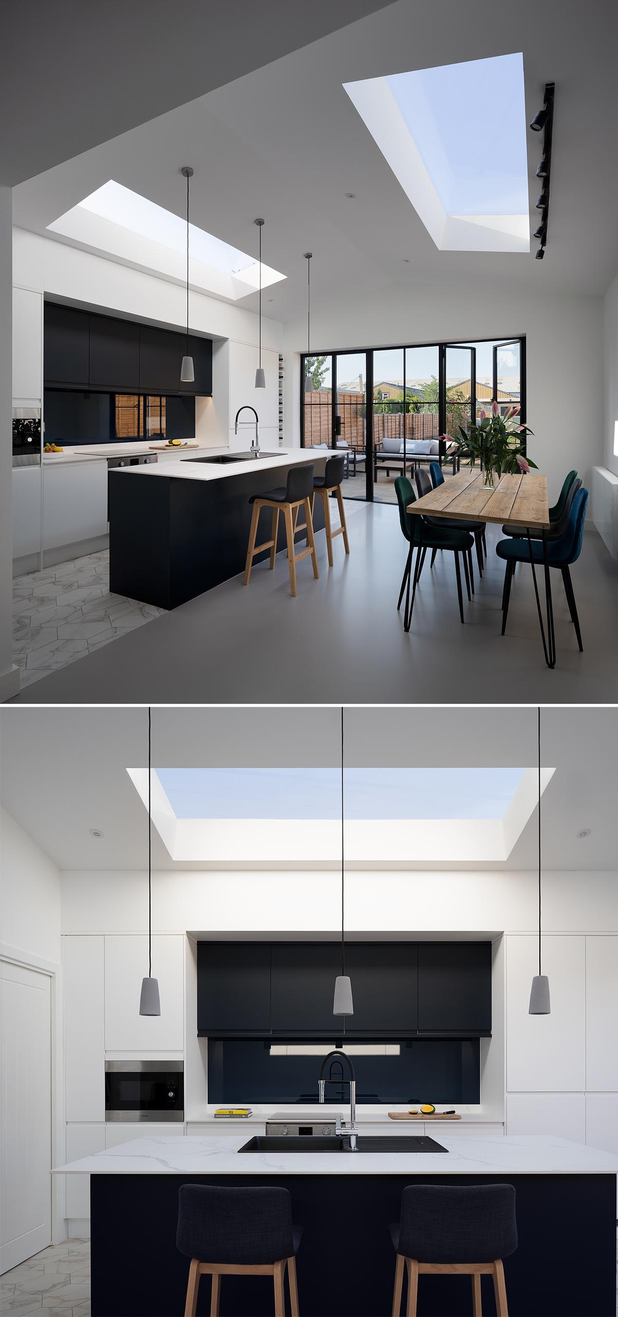 A modern open plan kitchen and dining room with a pitched ceiling and skylights.