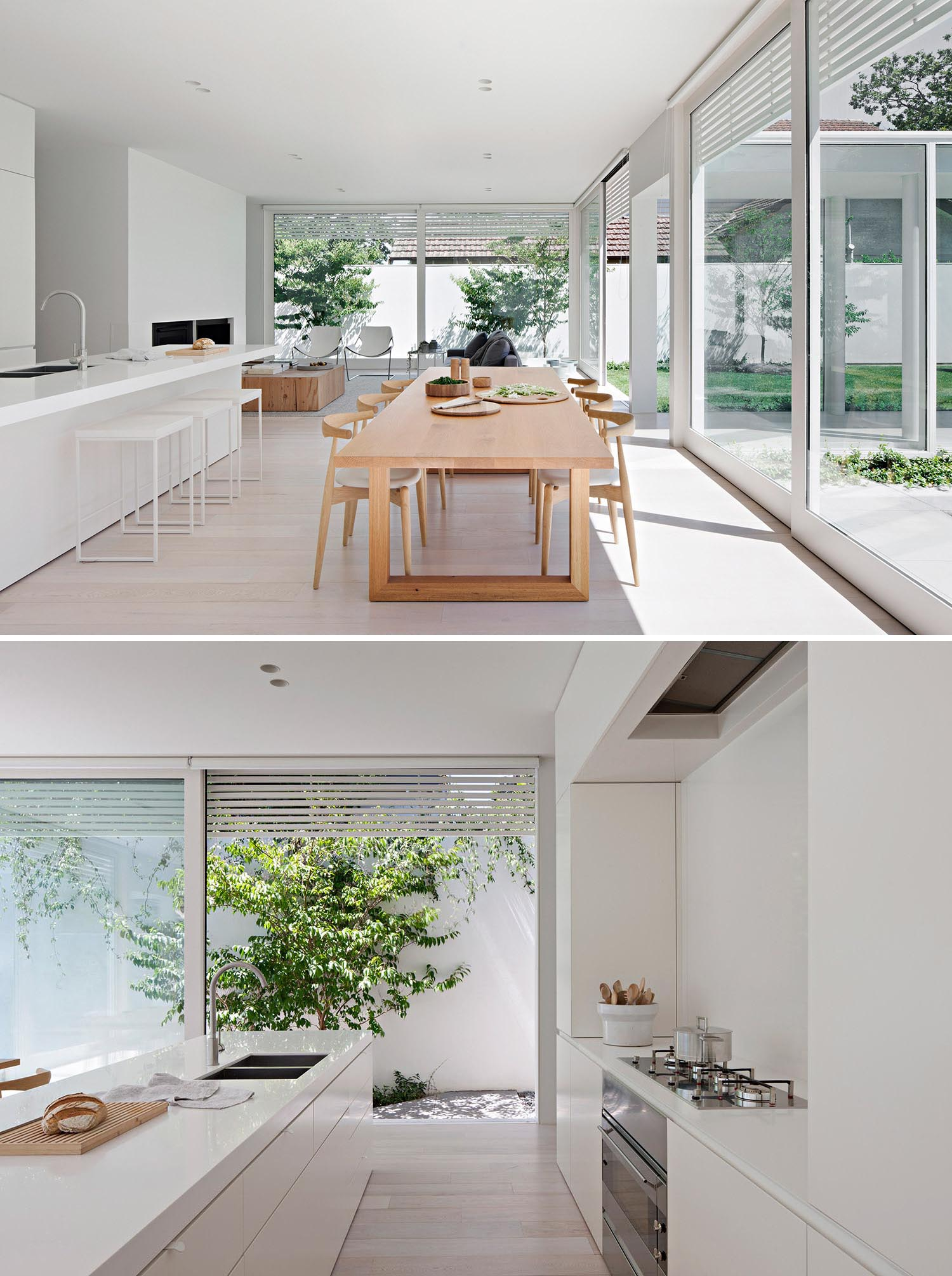 A modern open plan interior with a large wood dining table and minimalist white kitchen.