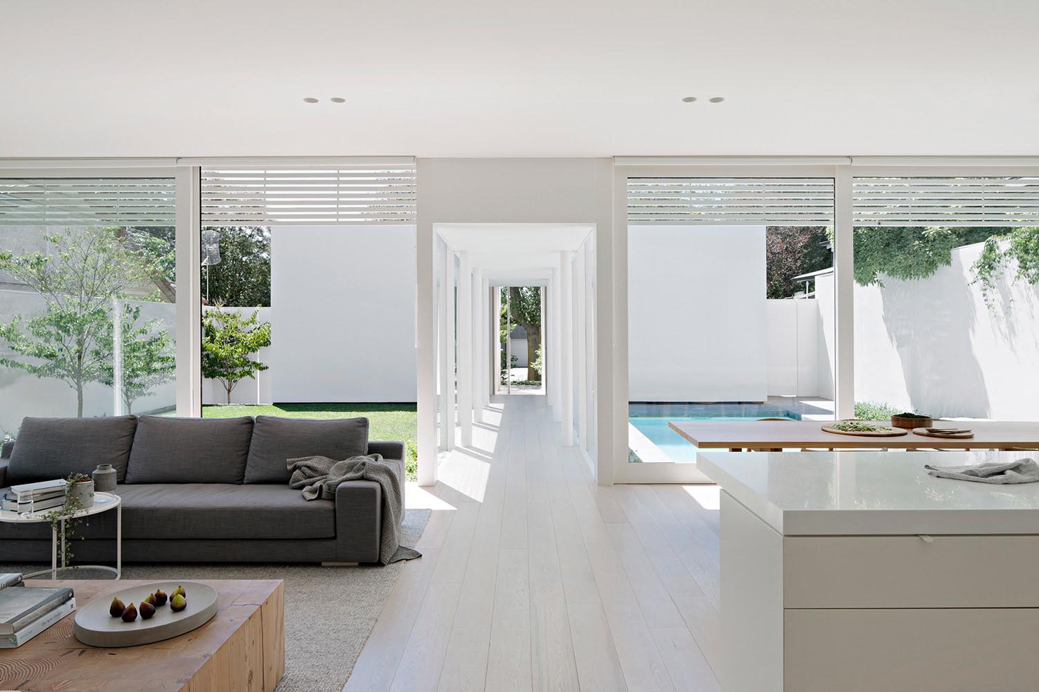 A modern open plan interior with large windows, light floors, and white walls.