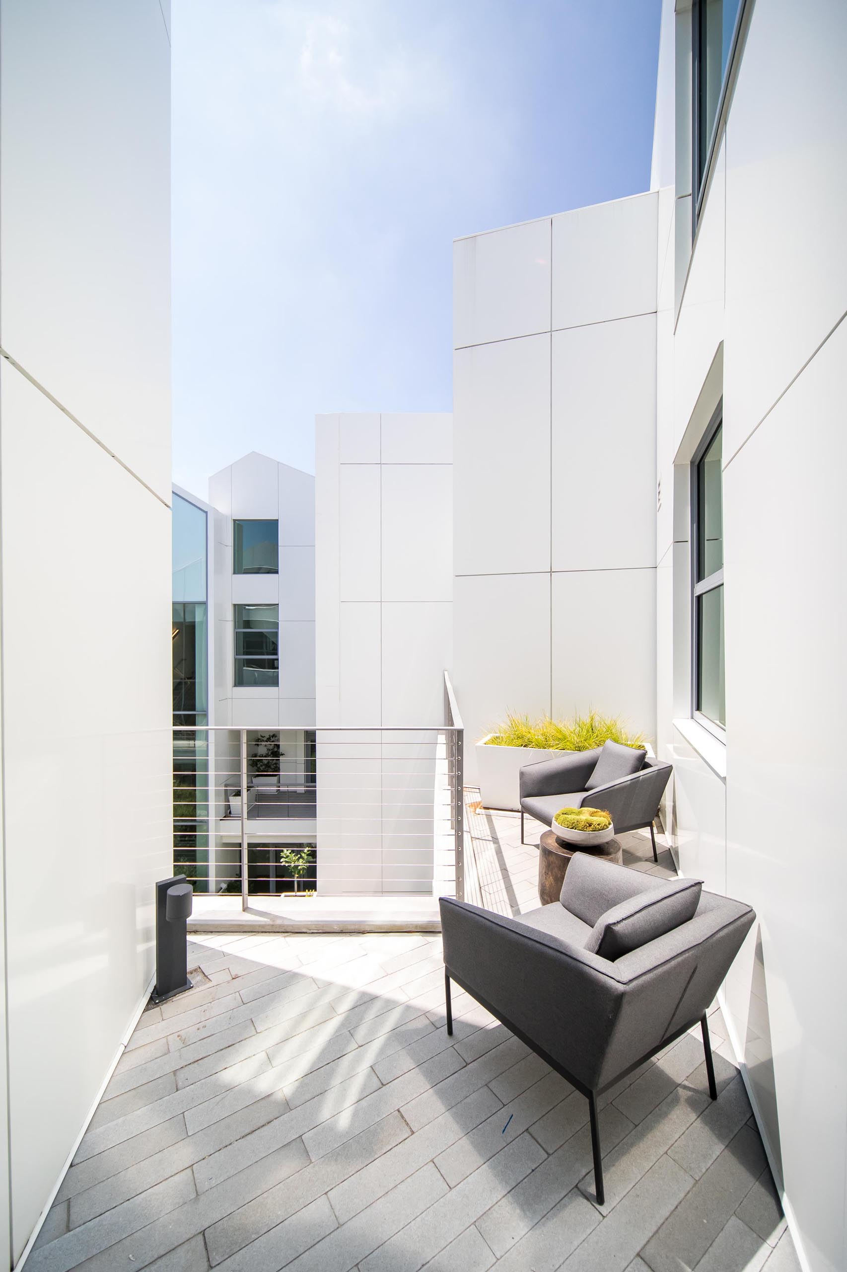 A small terrace with a pair of armchairs and a planter.
