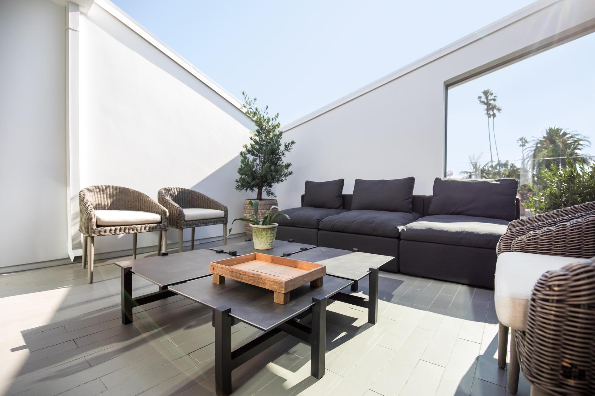 A modern terrace with a sofa, coffee table, and armchairs.