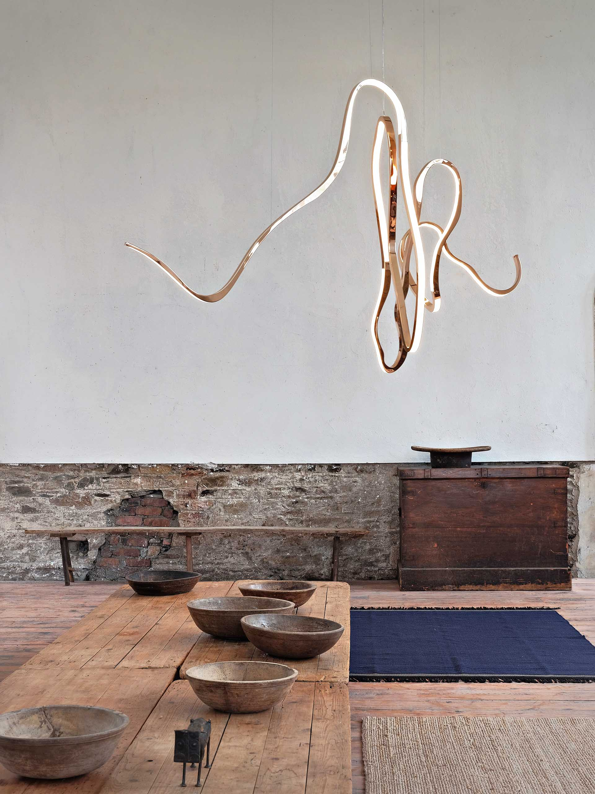 A modern sculptural light made from polished bronze, glass, and LEDs.