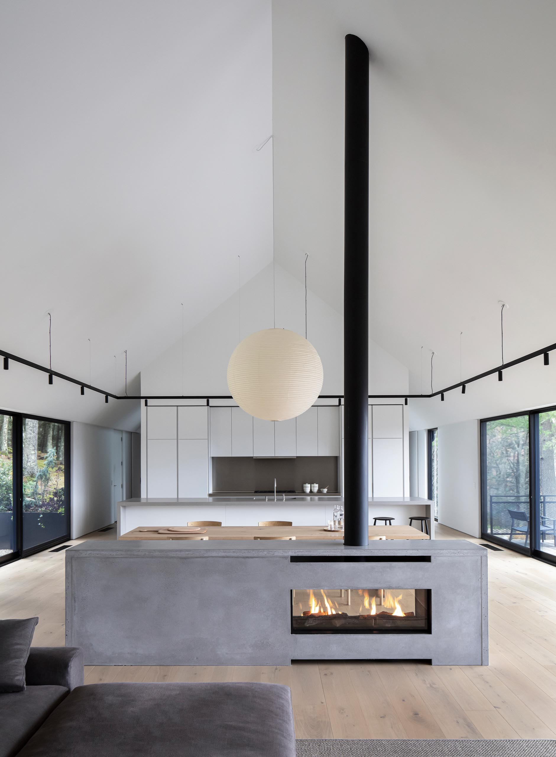 A modern house interior with a see-through fireplace with a concrete surround.