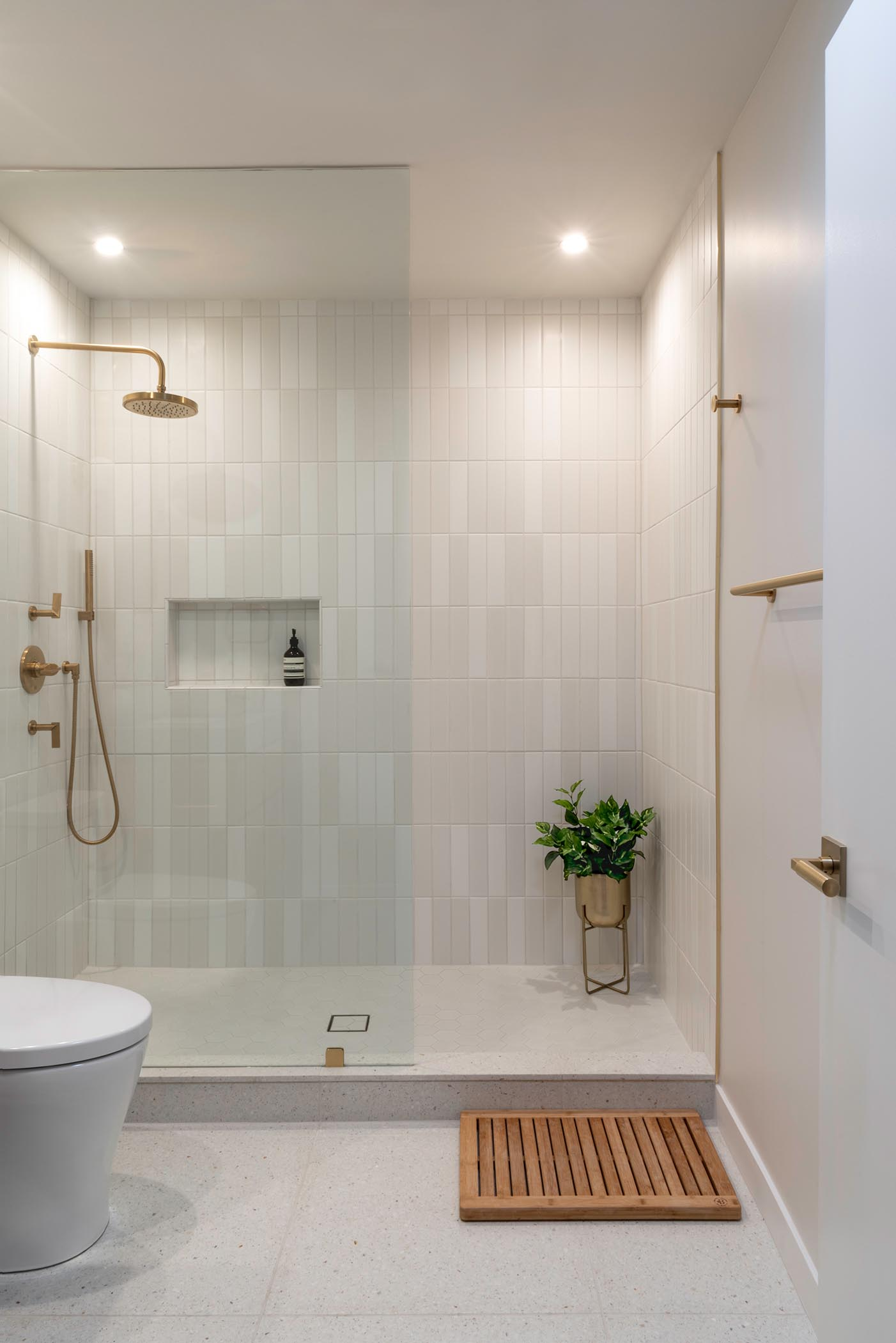 In this bathroom, there's a walk-in shower with shower niche and a seamless shower screen, white wall tiles, satin brass fixtures, and  Terrazo floor and shower curb.