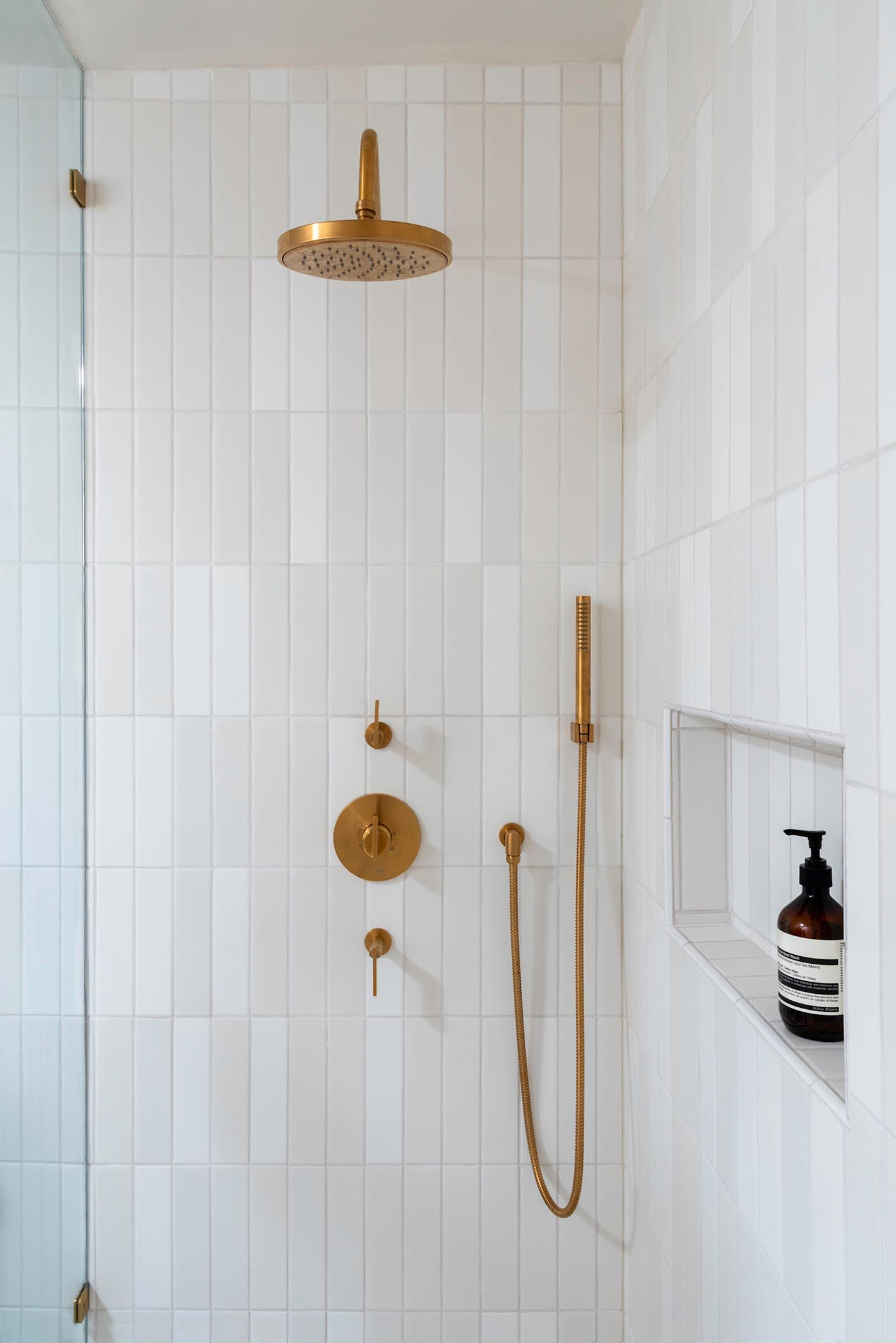 A modern white shower with a shelving niche and brass hardware.