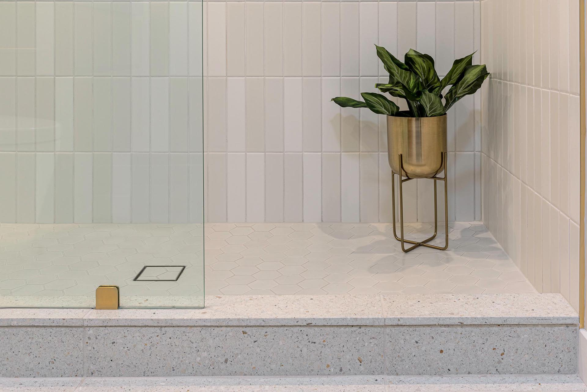 This modern bathroom has a Terrazo floor and shower curb.