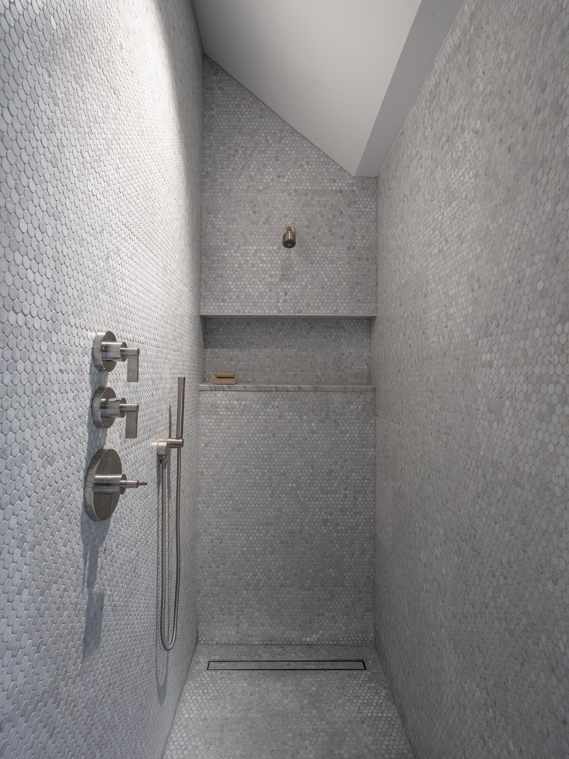 A modern shower with floor-to-ceiling grey penny tiles, a linear shower drain, and a built-in shelf.