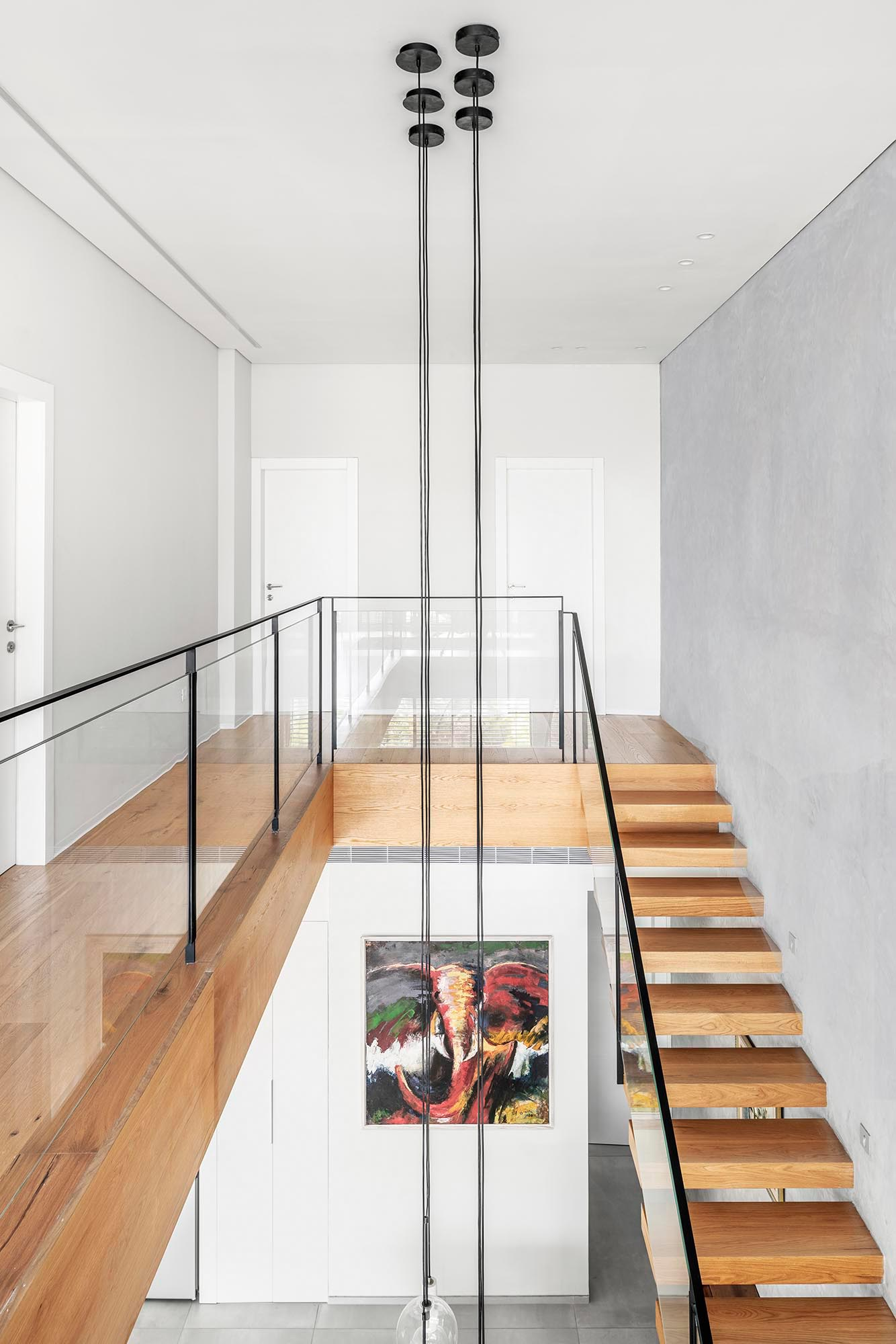 The top of this wood staircase opens to a walkway that leads to a small sitting room. The railing, composed of iron and glass, completes the clean and minimalist look.