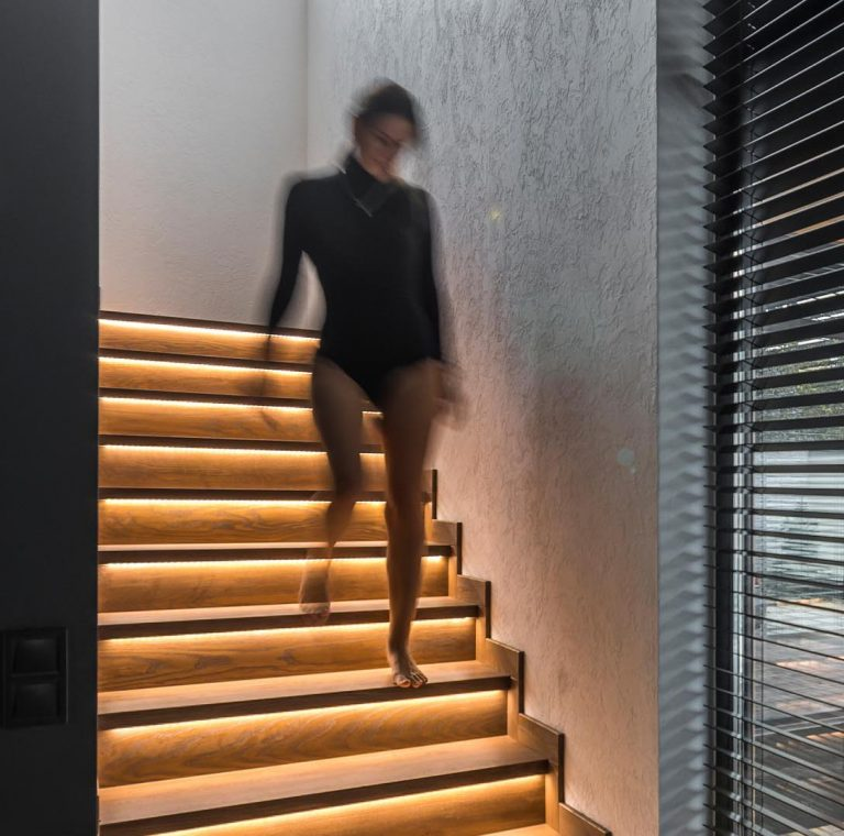 A Strip Of LED Lights Under The Stairs Of This Home Adds A Warm Glow To The Interior