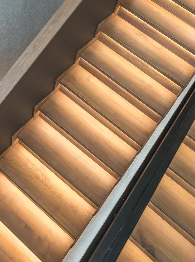 A wood staircase design with hidden lighting.