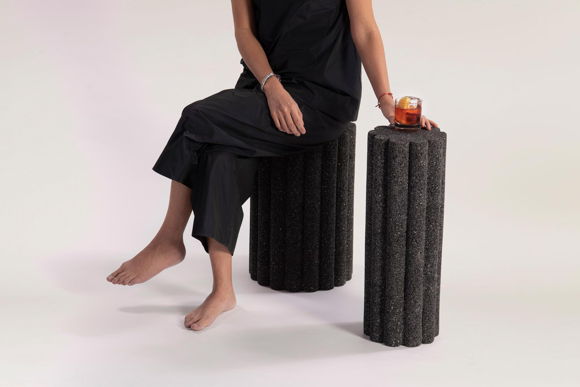 Modern black side tables and stools made from volcanic rock.