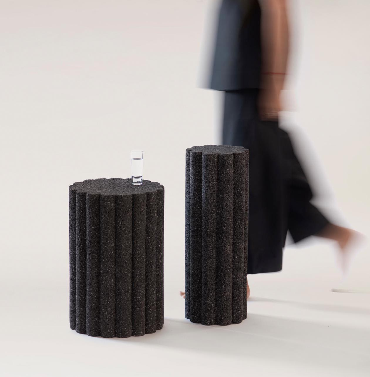 A collection of modern black side tables and stools made from volcanic rock.