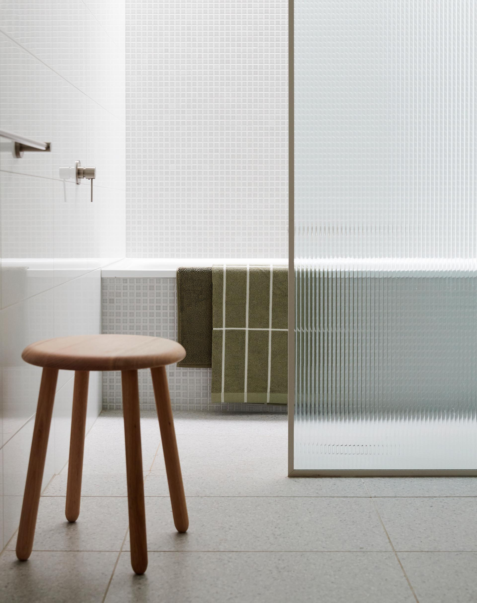 In this modern bathroom, small square tiles cover the wall and the exterior of the bath.