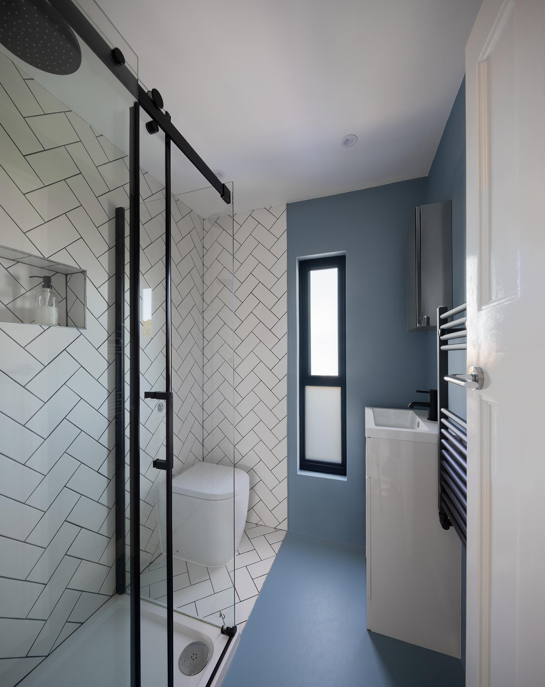 A modern bathroom with white tiles in a herringbone pattern, black hardware, and narrow vanity.