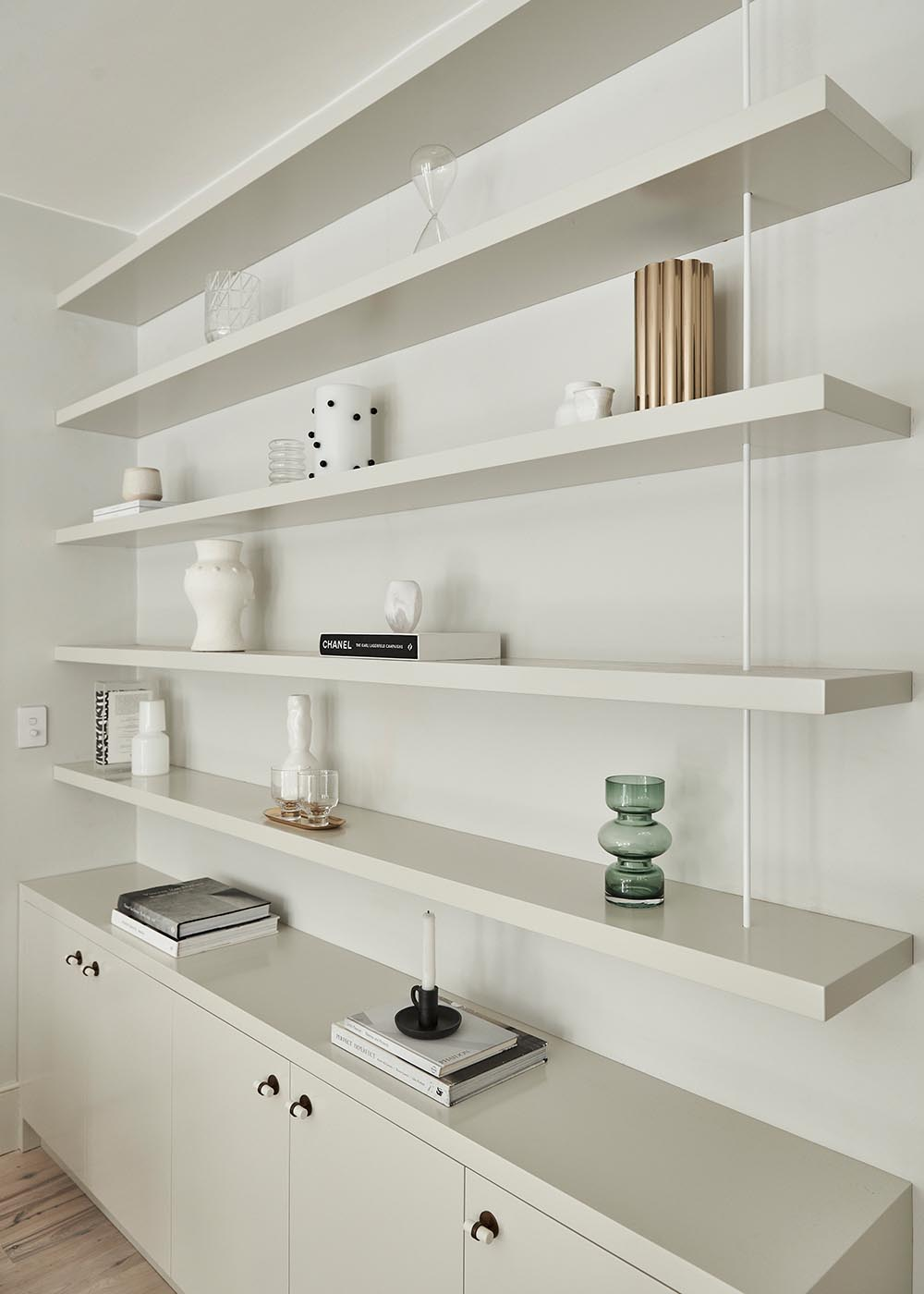 Custom cabinetry and wall shelving almost seamlessly blend into the wall, allowing the decorative objects to stand out.