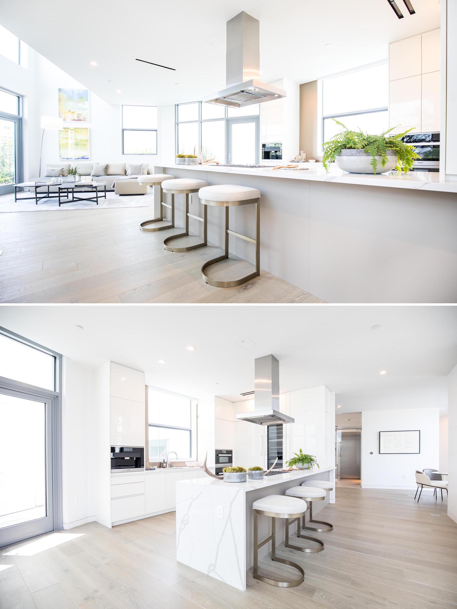 A modern open plan white kitchen with a large island.