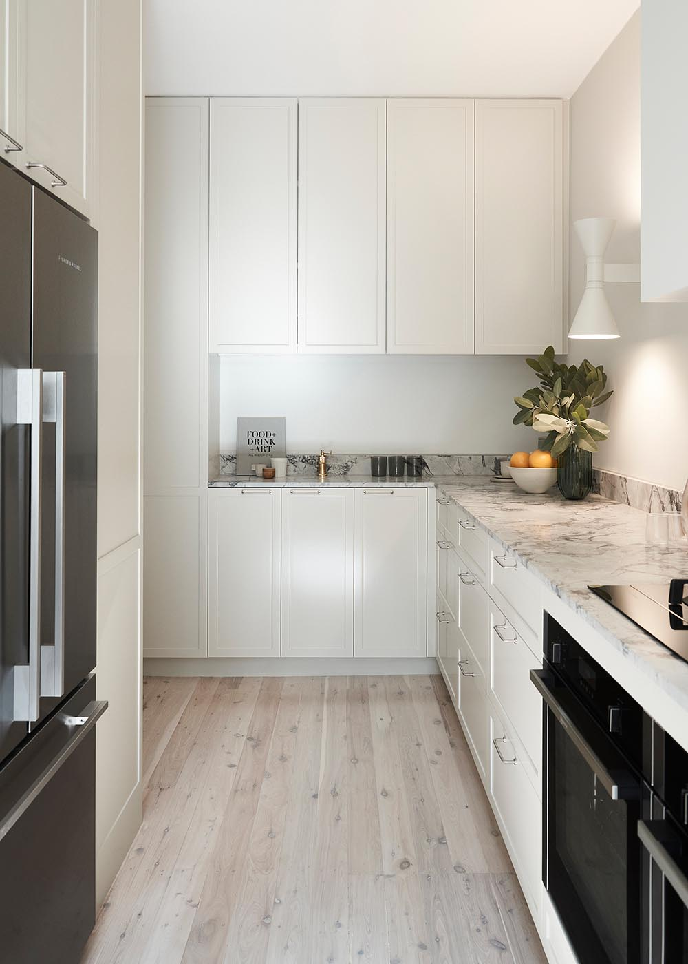 This contemporary kitchen features stone counters, warm textures, handmade tiles, and pale toned cabinetry that complement the other design choices throughout the apartment.