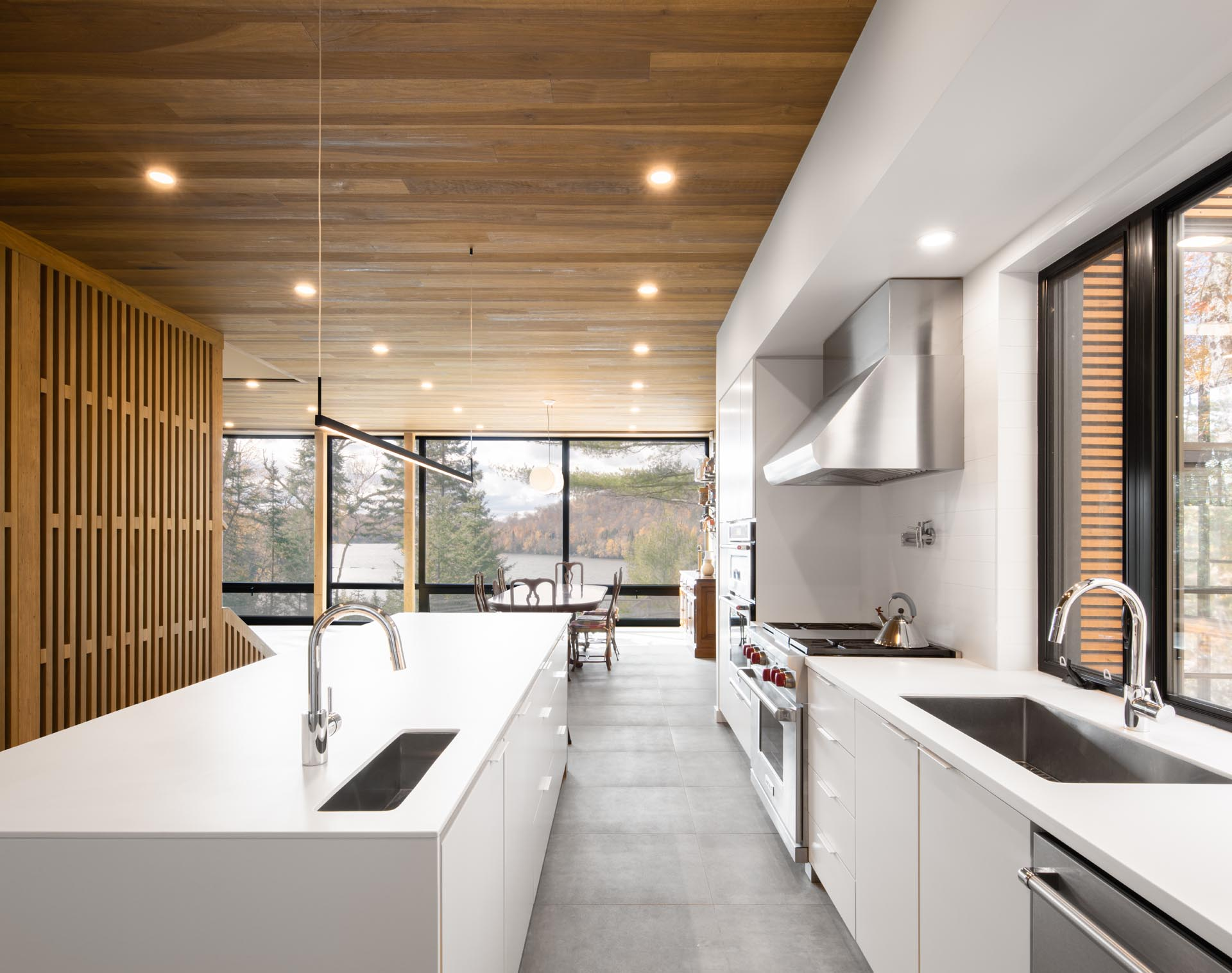 A large white kitchen with an island and an open plan dining area both enjoy views of the lake through floor-to-ceiling windows.