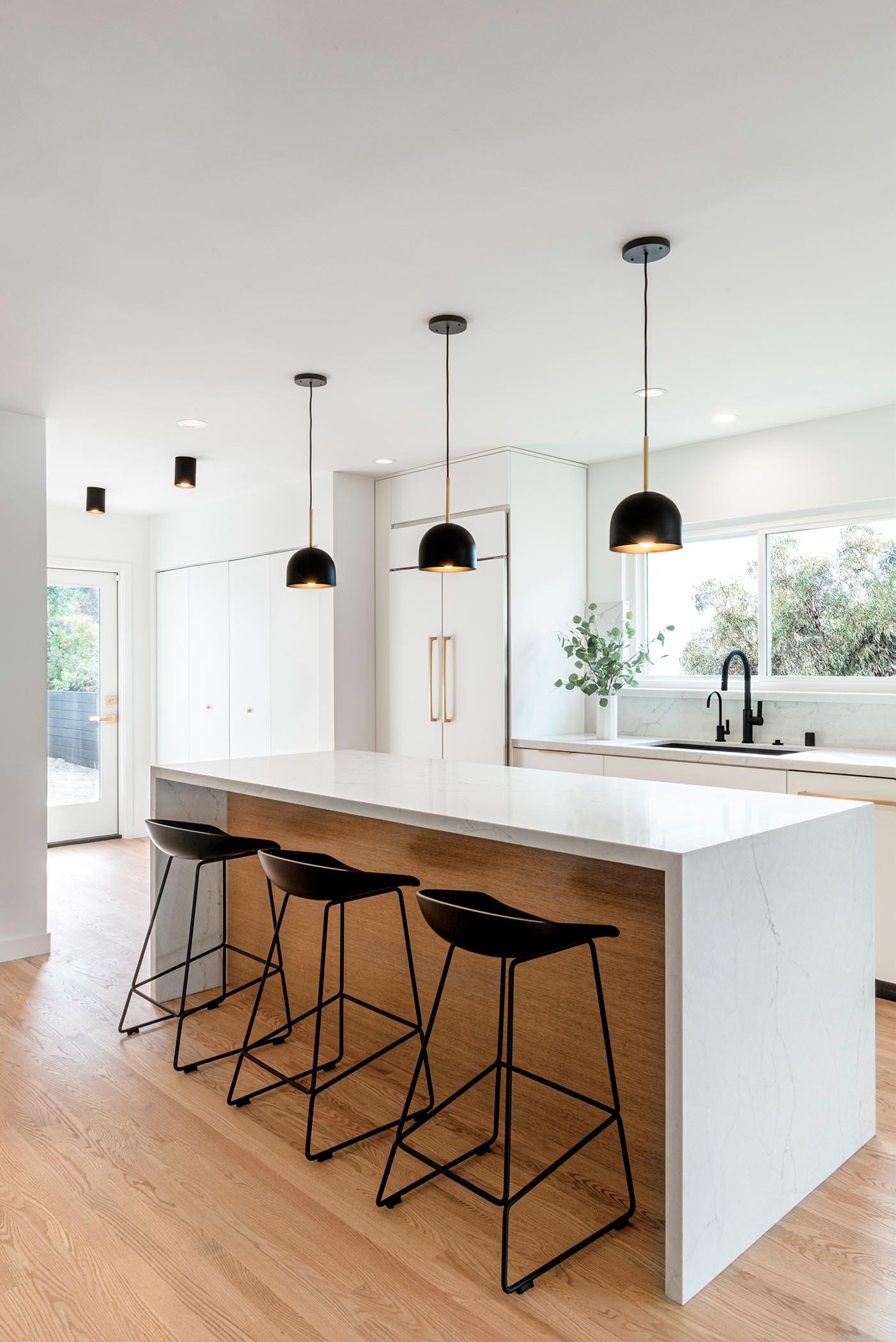 Three black pendant lights by Cedar & Moss hang above a modern kitchen island which complement the black stools. The design of the island allows the stools to be neatly tucked away when not being used.