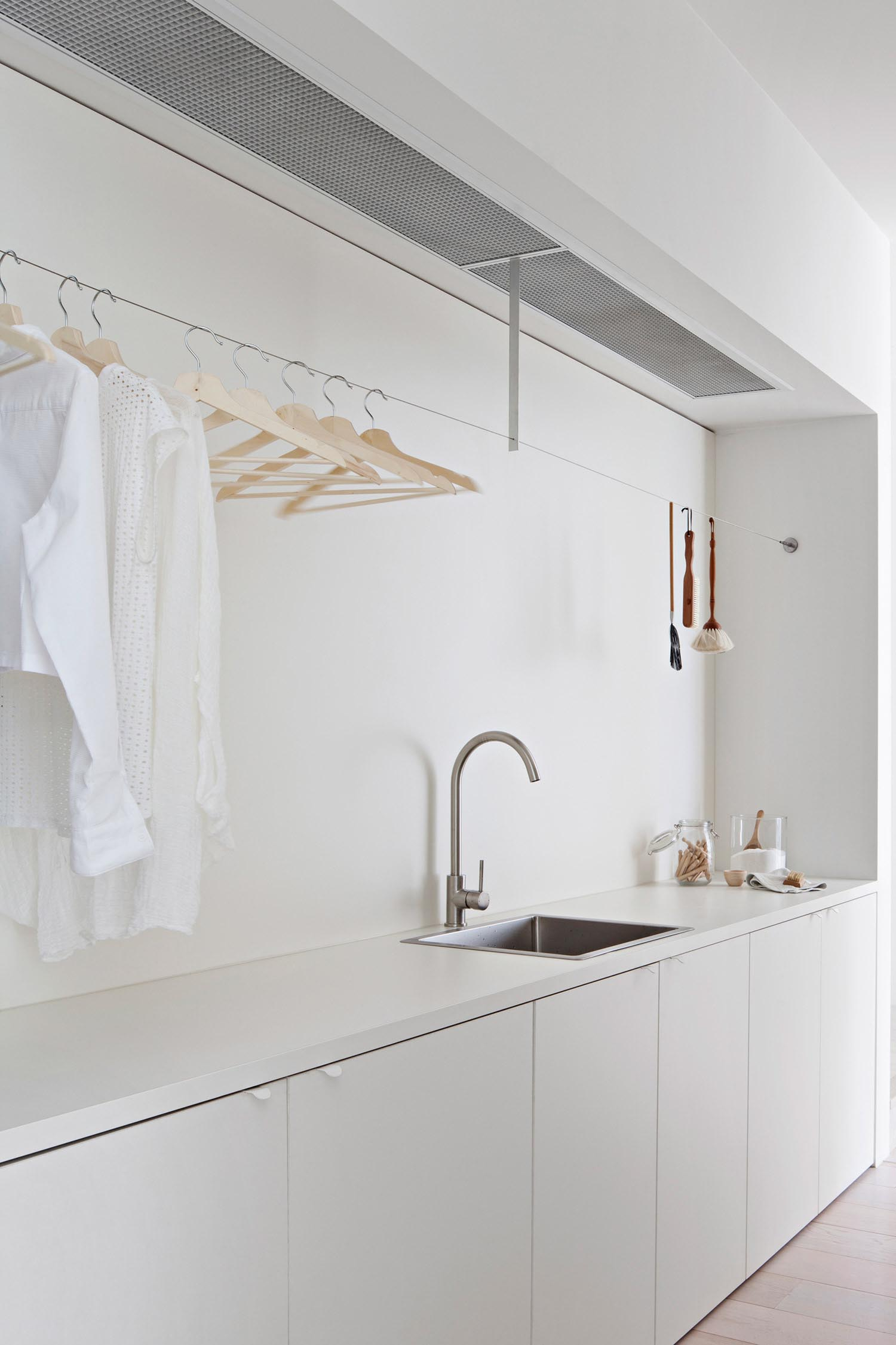 A modern white laundry room with sink, cabinets, and a place to hang clothes to dry.
