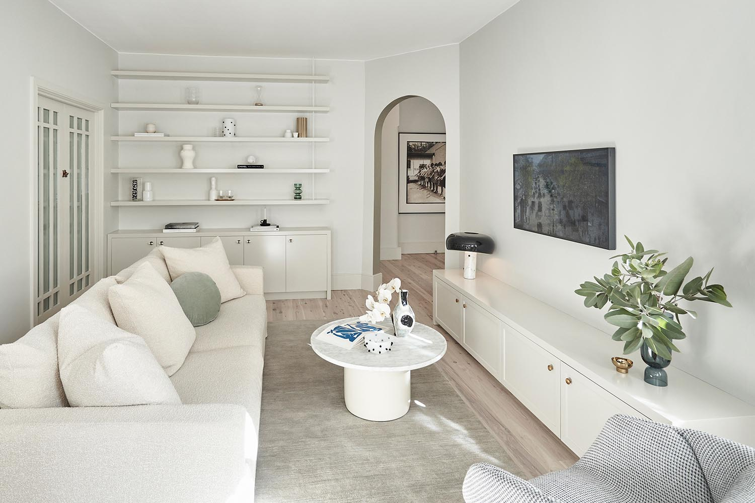 A white living room with custom cabinets and shelving.