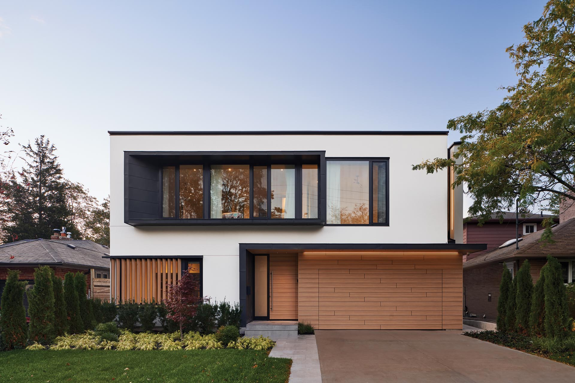 The exterior of this modern house features a facade of white stucco walls and black metal accent panels, which were paired with warm oak-look phenolic panels.