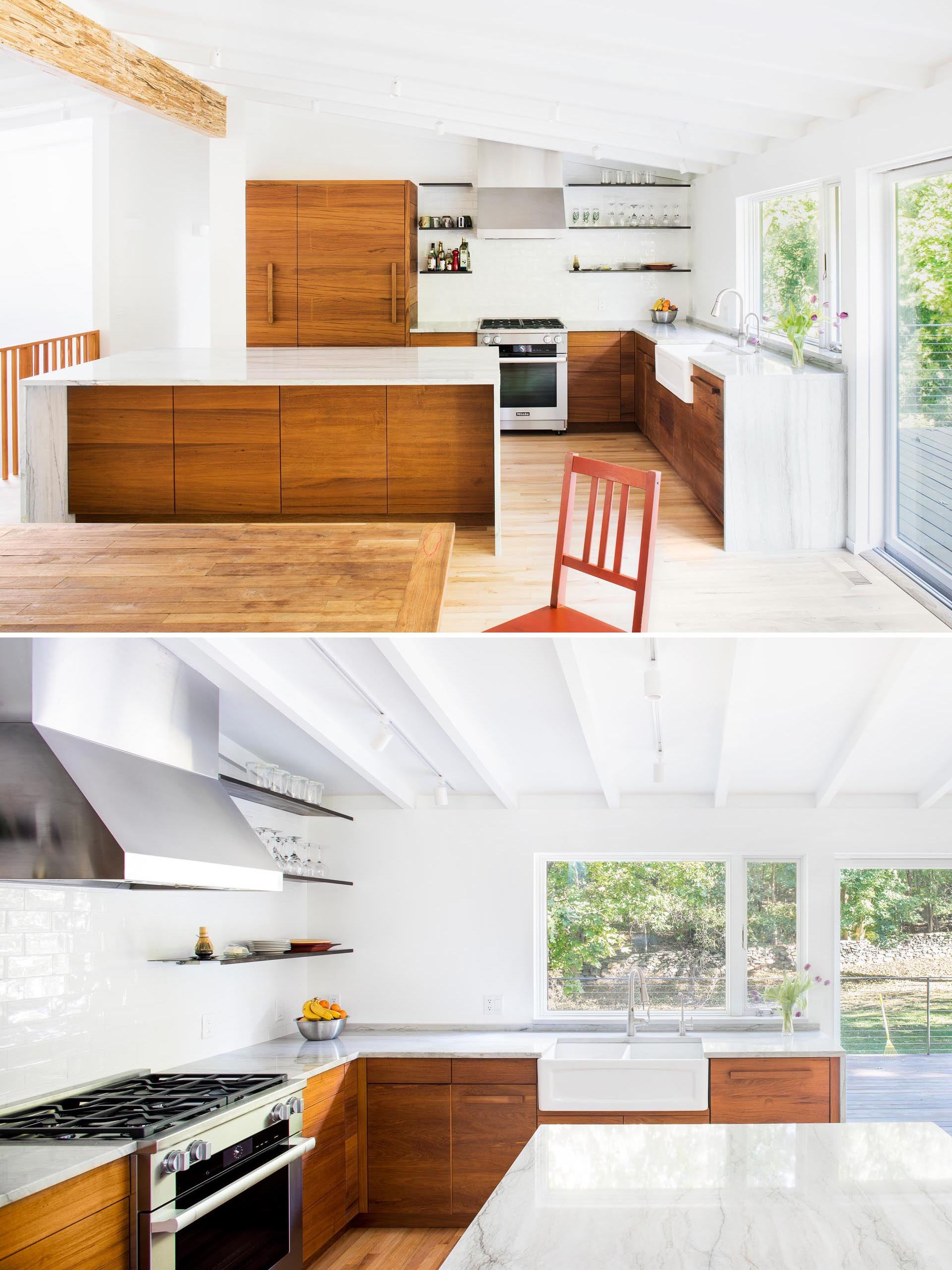 The remodeled kitchen includes wood cabinets, an island with a waterfall countertop, a white apron sink, and floating wood shelves.