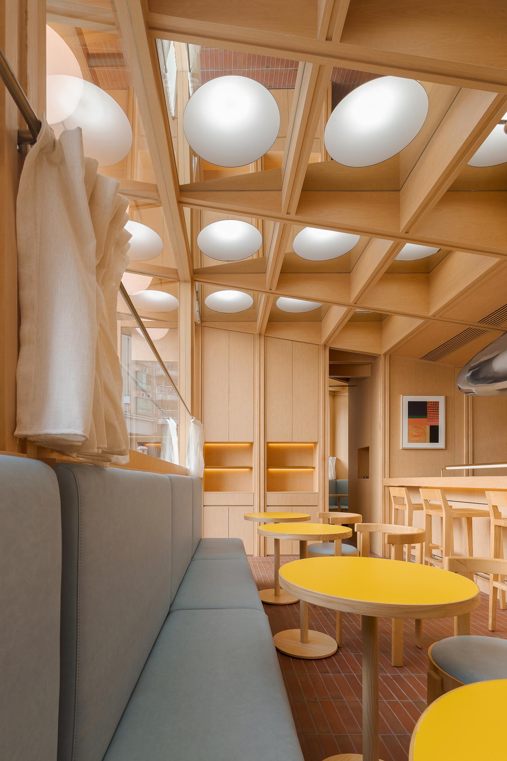 A modern cafe and bar with a wood interior, banquette seating, and bright yellow tables.
