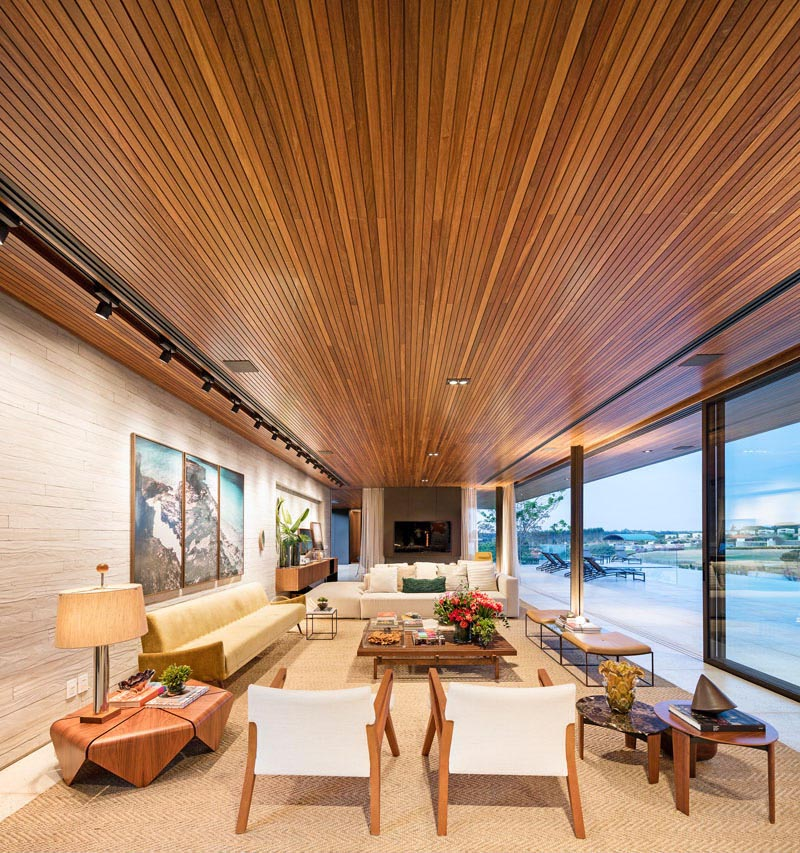 A modern living room with an uninterrupted wood ceiling.