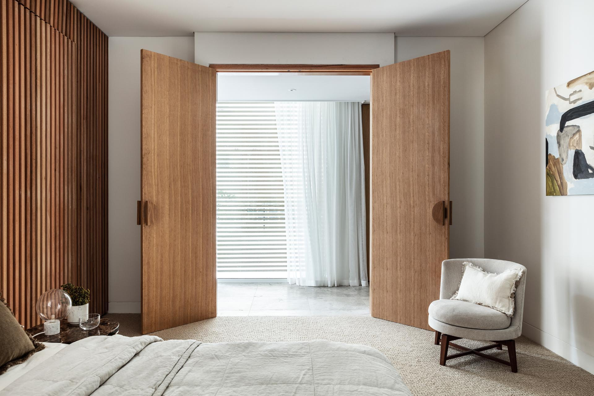 Two wood doors open to this modern bedroom, where a wood slat wall has been used to create an accent wall behind the bed.