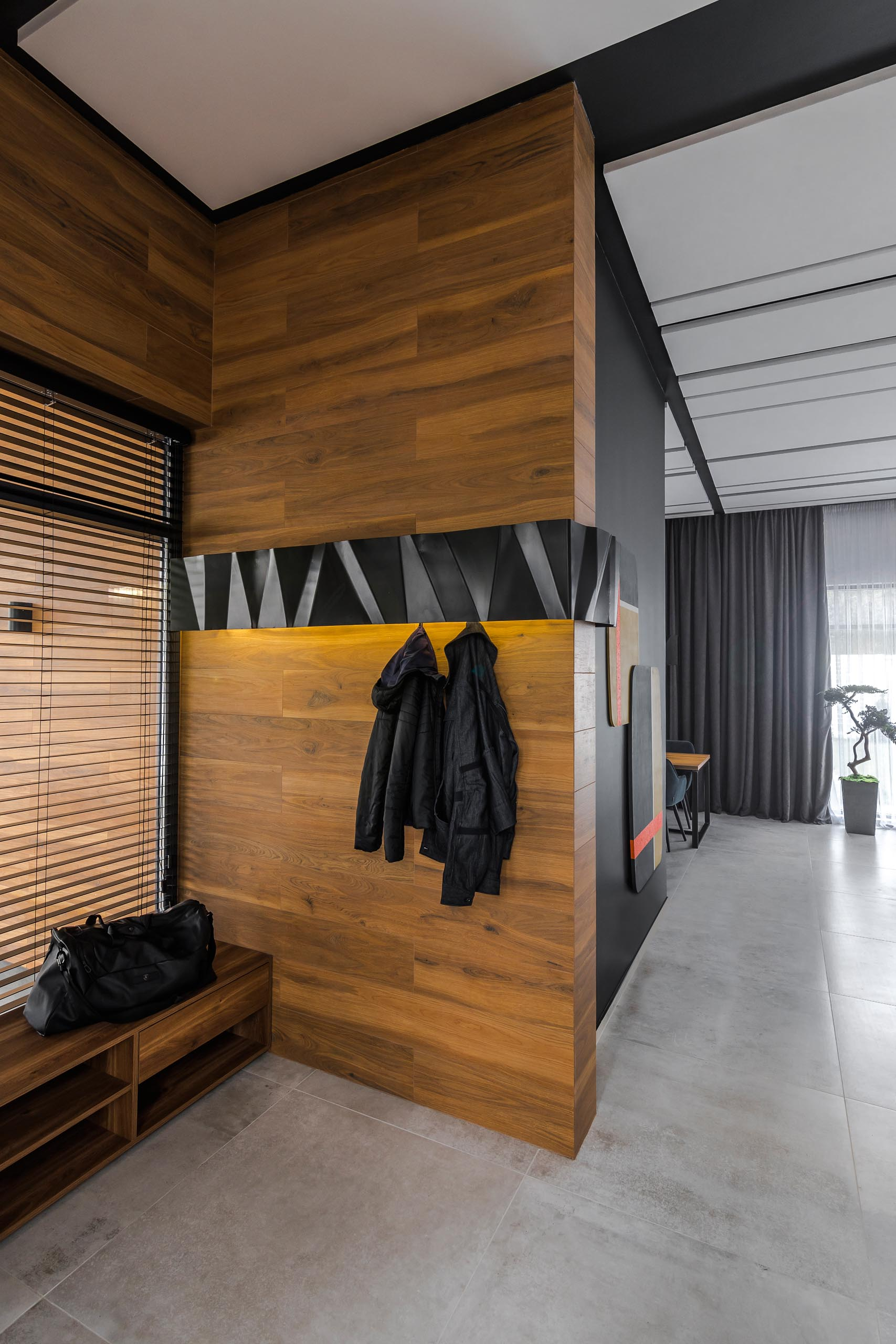 A modern wood entryway with a black metal accent that has hidden hooks and lighting.
