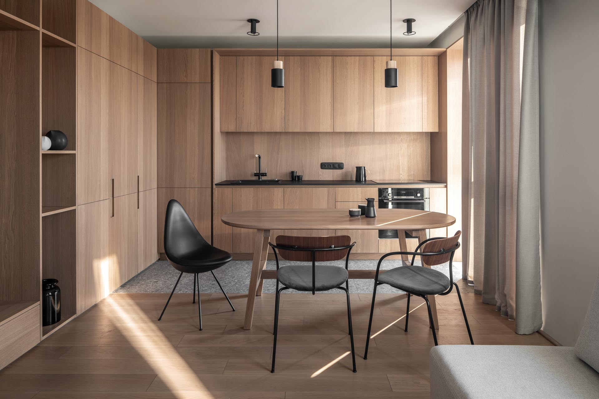 A modern wood kitchen with minimalist cabinets, black hardware, and an eat-in dining table.