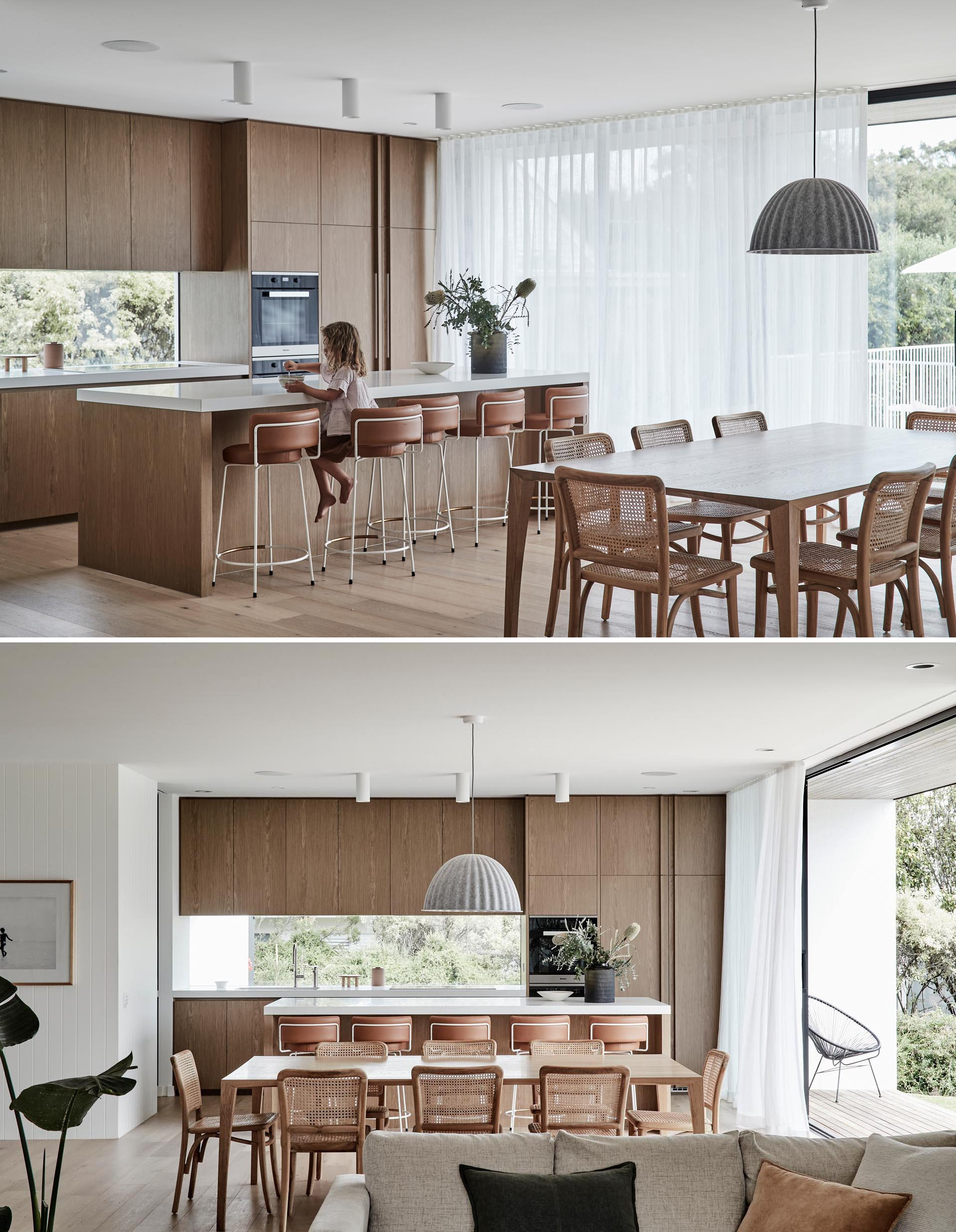 Warm wood dining chairs and kitchen cabinets add a natural element to the interior design of this modern home, while light brown leather stools provide seating at the island.
