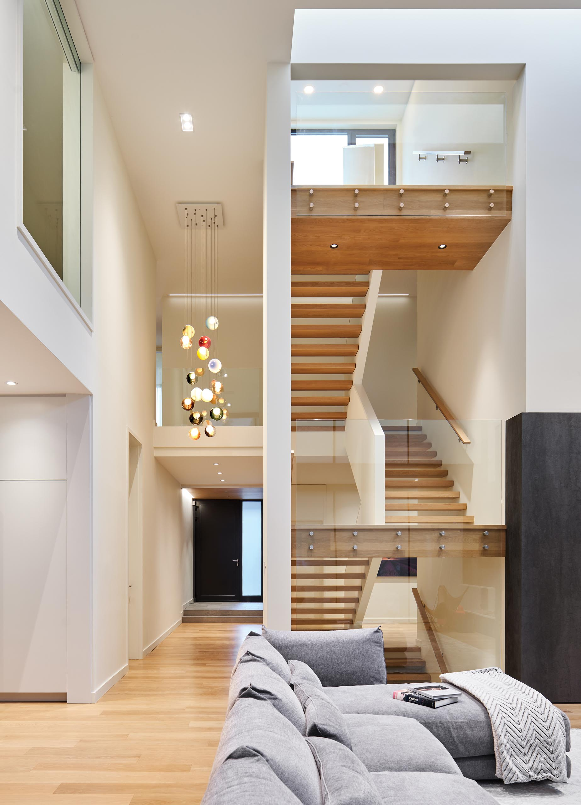 An open wood staircase with glass railings that connects the multiple levels of the home. A colorful accent has been added with the inclusion of suspended Bocci lights.